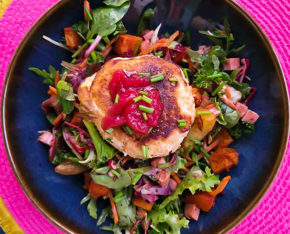 Salade avec des carottes, des tomates, du jambon, et des patates douces avec en son centre la tomme rôtie et la confiture de fraise.