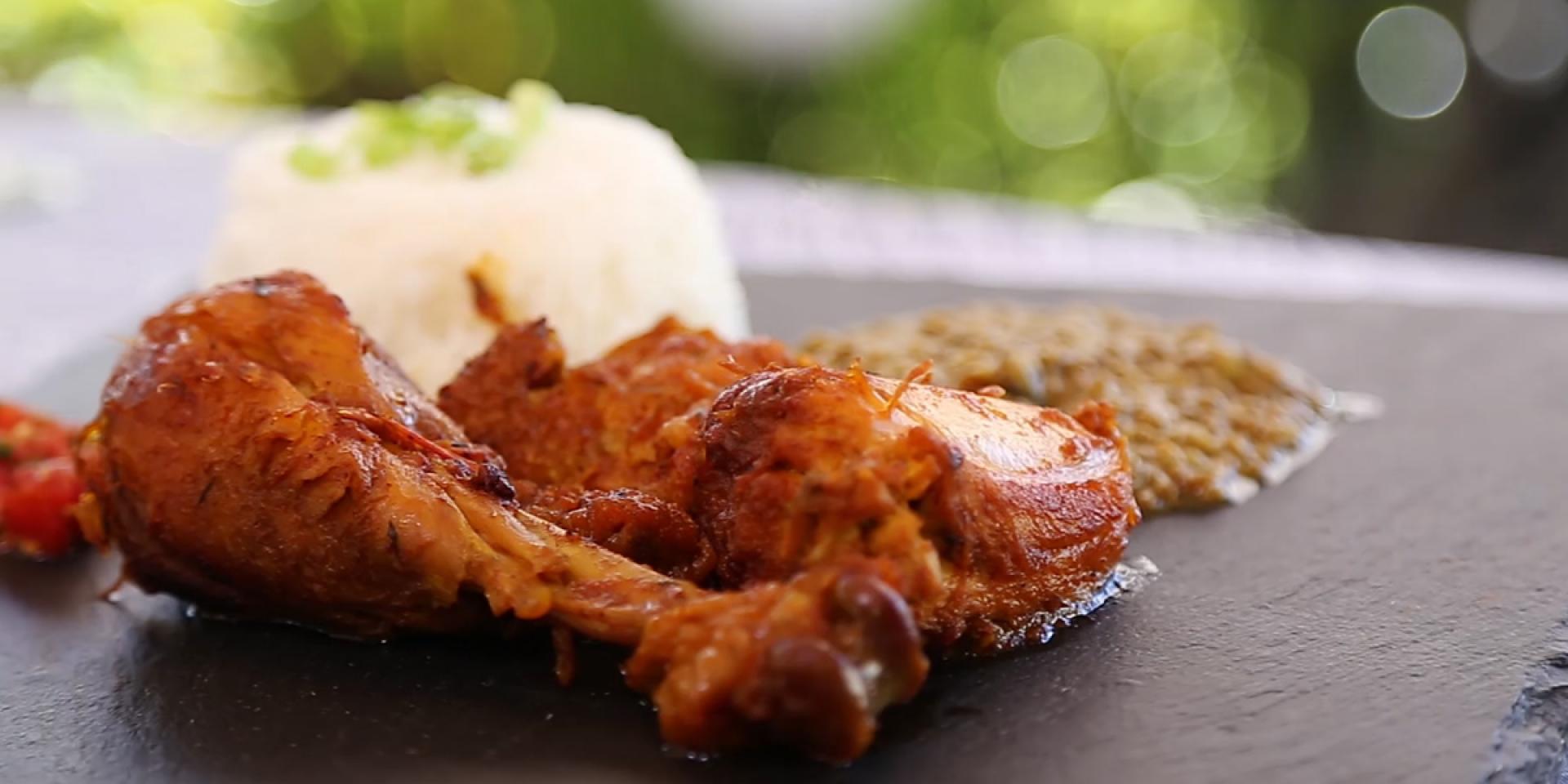 Cuisse de poulet en premier plan avec une boule de riz à l'arrière présenté sur une ardoise