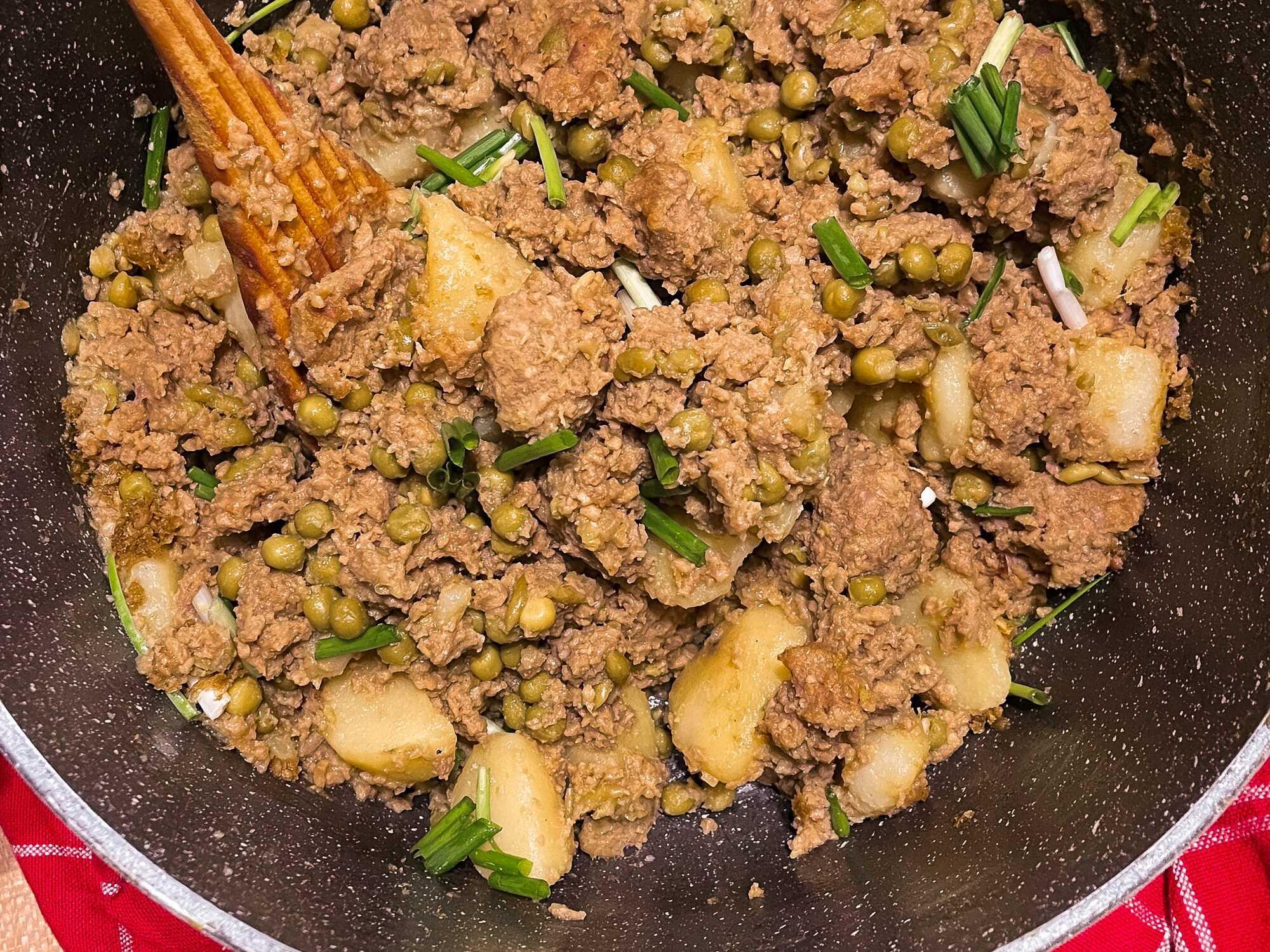 Viande hachée mélangée avec des petits pois et pommes de terre dans une poêle noire posée sur un torchon rouge.