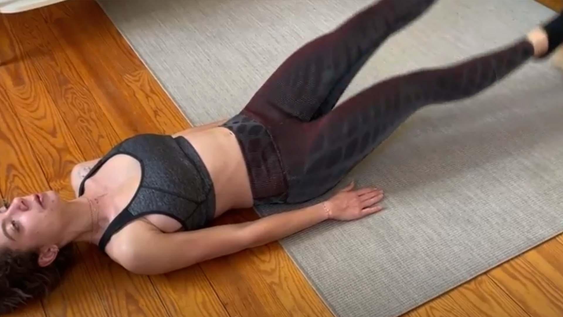 Femme exécutant des battements de jambes pour le travail des abdominaux allongée sur un tapis gris