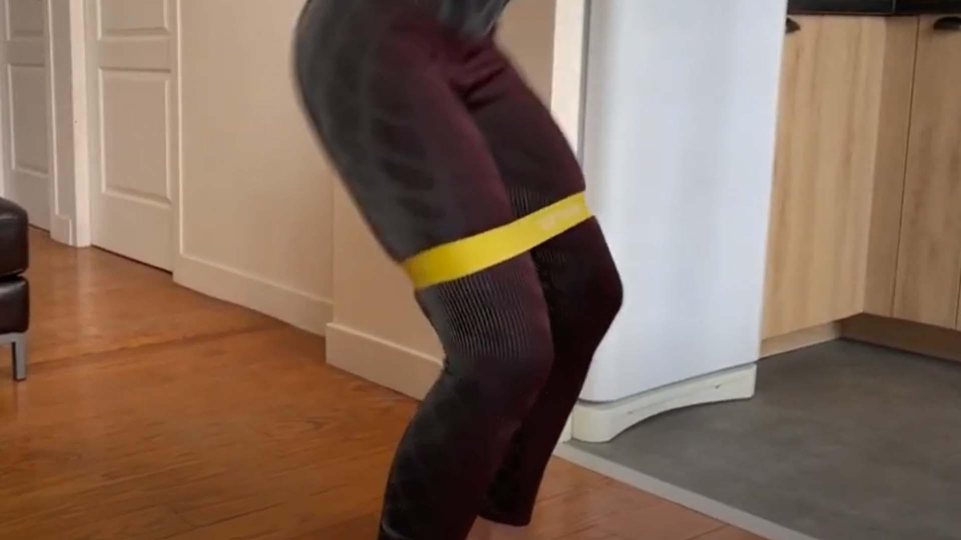 Femme réalisant des squat avec un booty band jaune