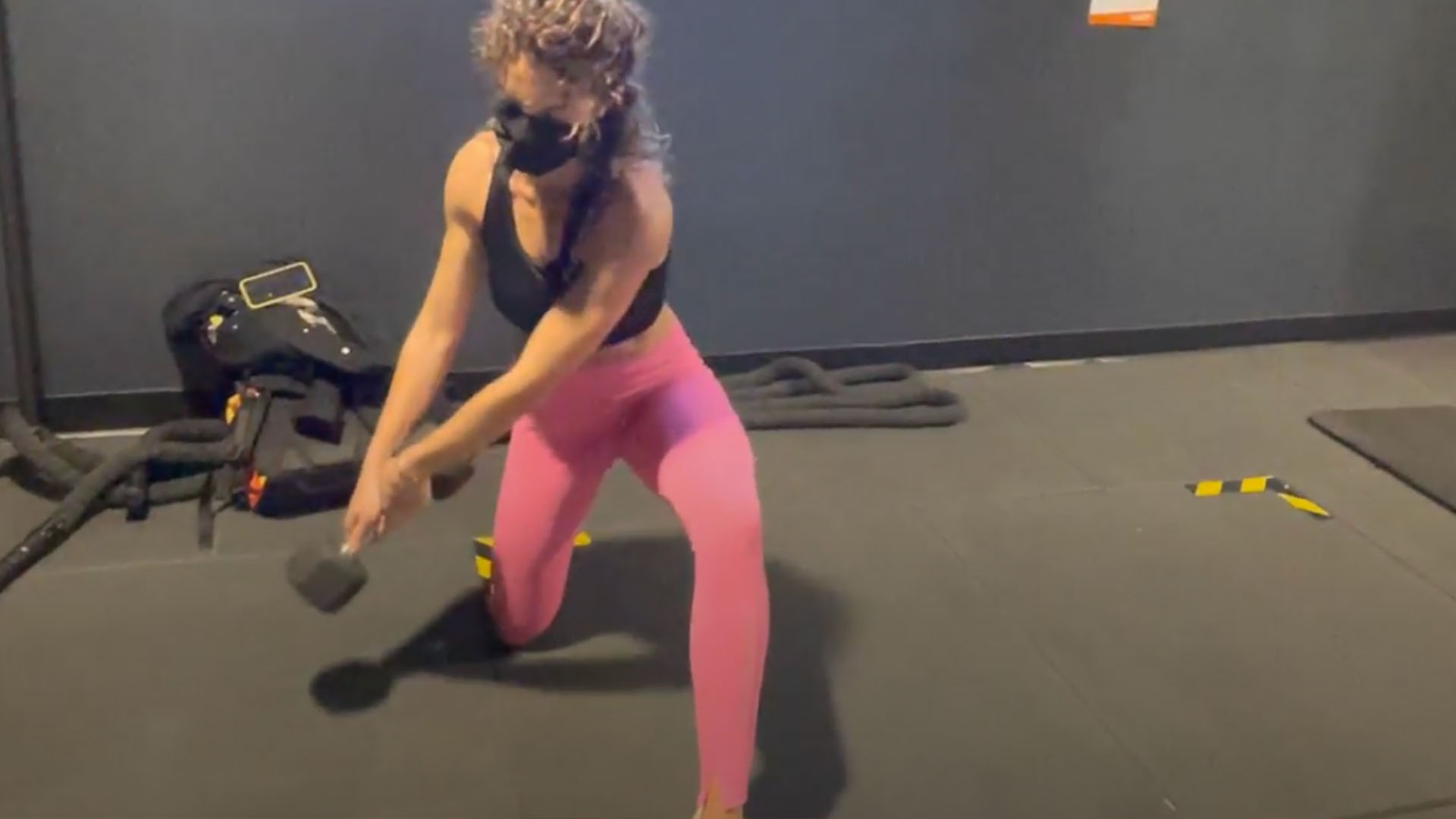 Femme exécutant un exercice pour les obliques avec un haltère