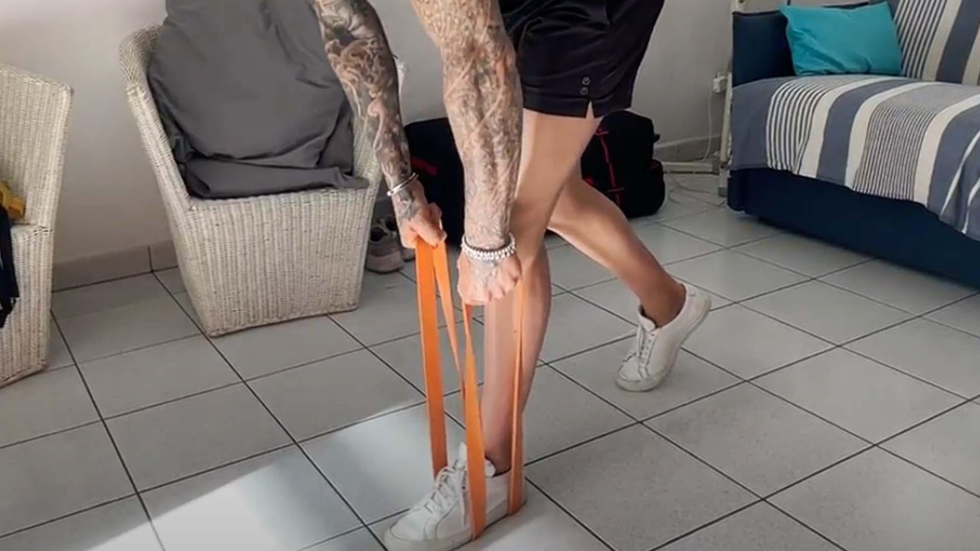 Homme exécutant un romanian deadlift sur une jambe avec un élastique orange