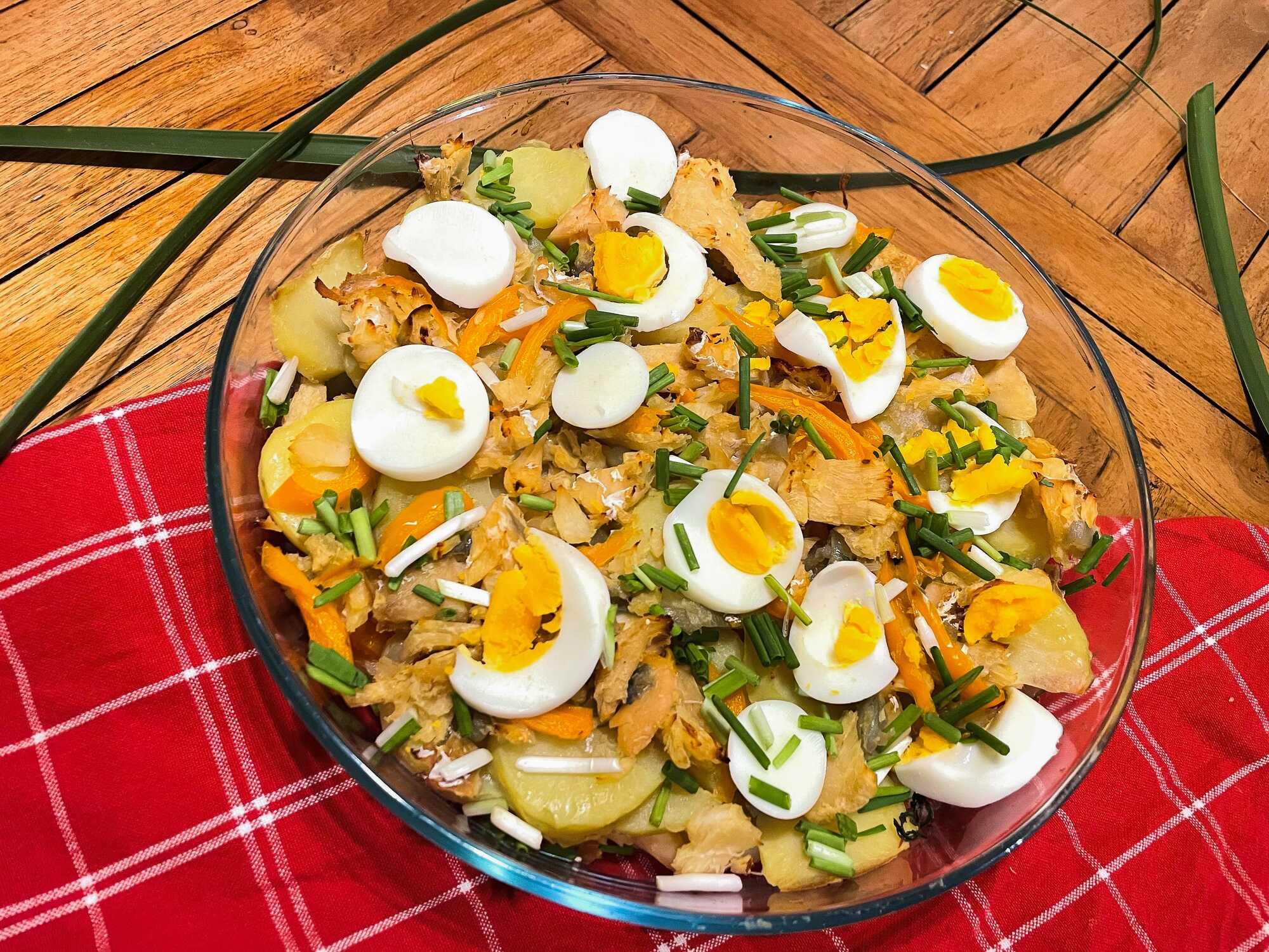 La morue, les oeufs et les pommes de terre parsemés de ciboulette sont présentés dans un grand saladier transparent.