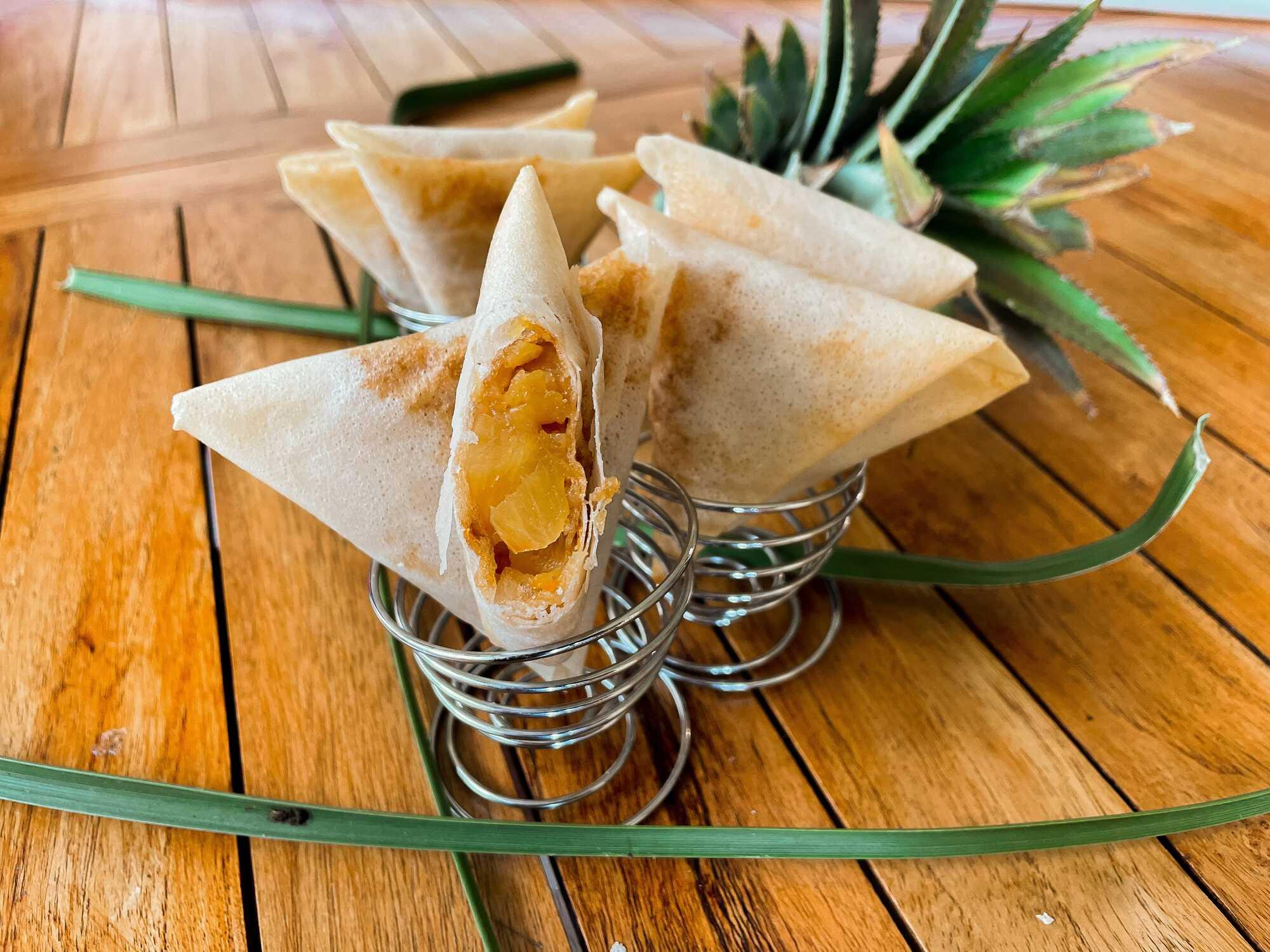 Sur une table en bois, les samoussas à l'ananas sont présentés dans des petits paniers en inox.