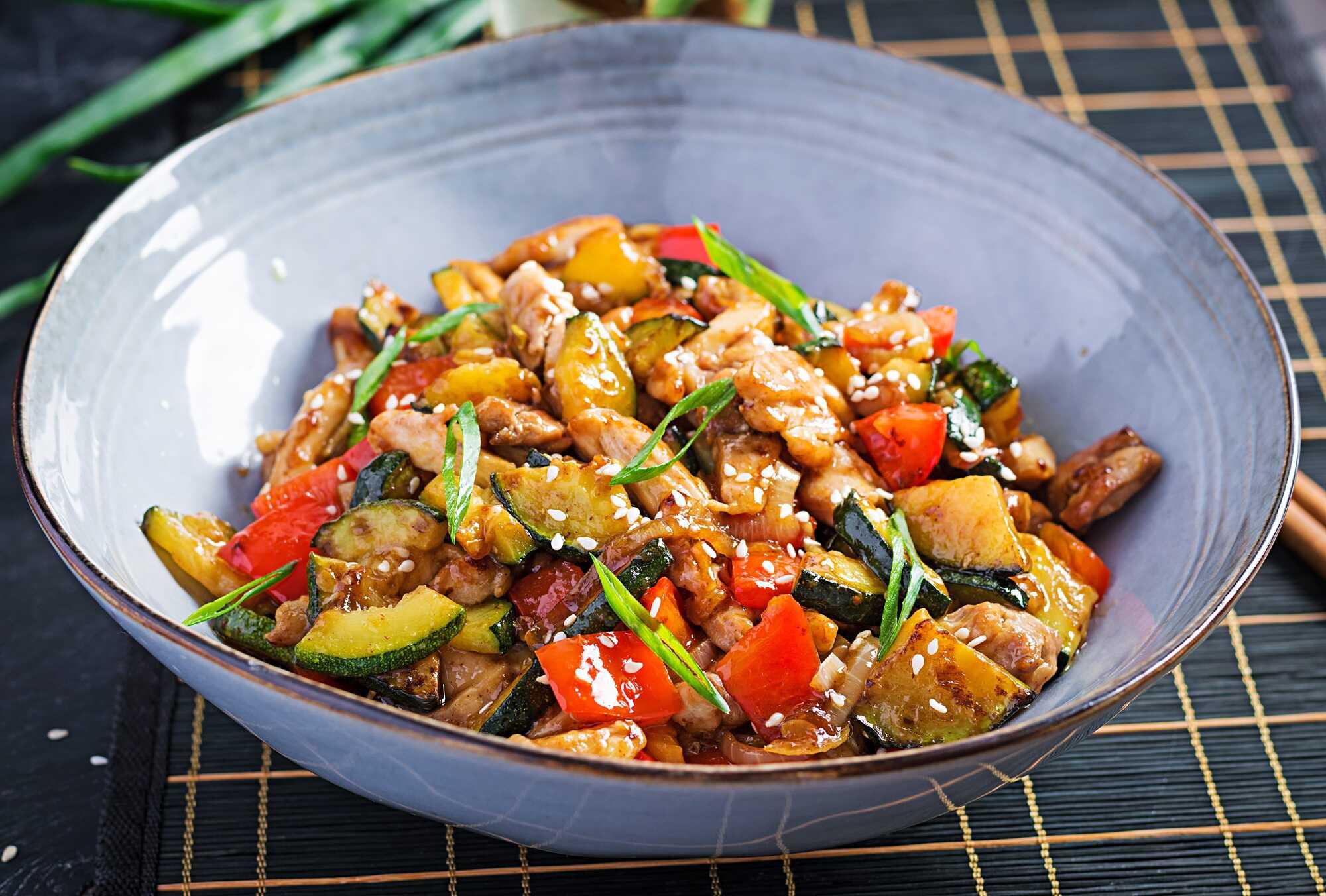 Les légumes et le poulet sont sautés préalablement, et ils sont présentés dans un bol bleu sur un set noir