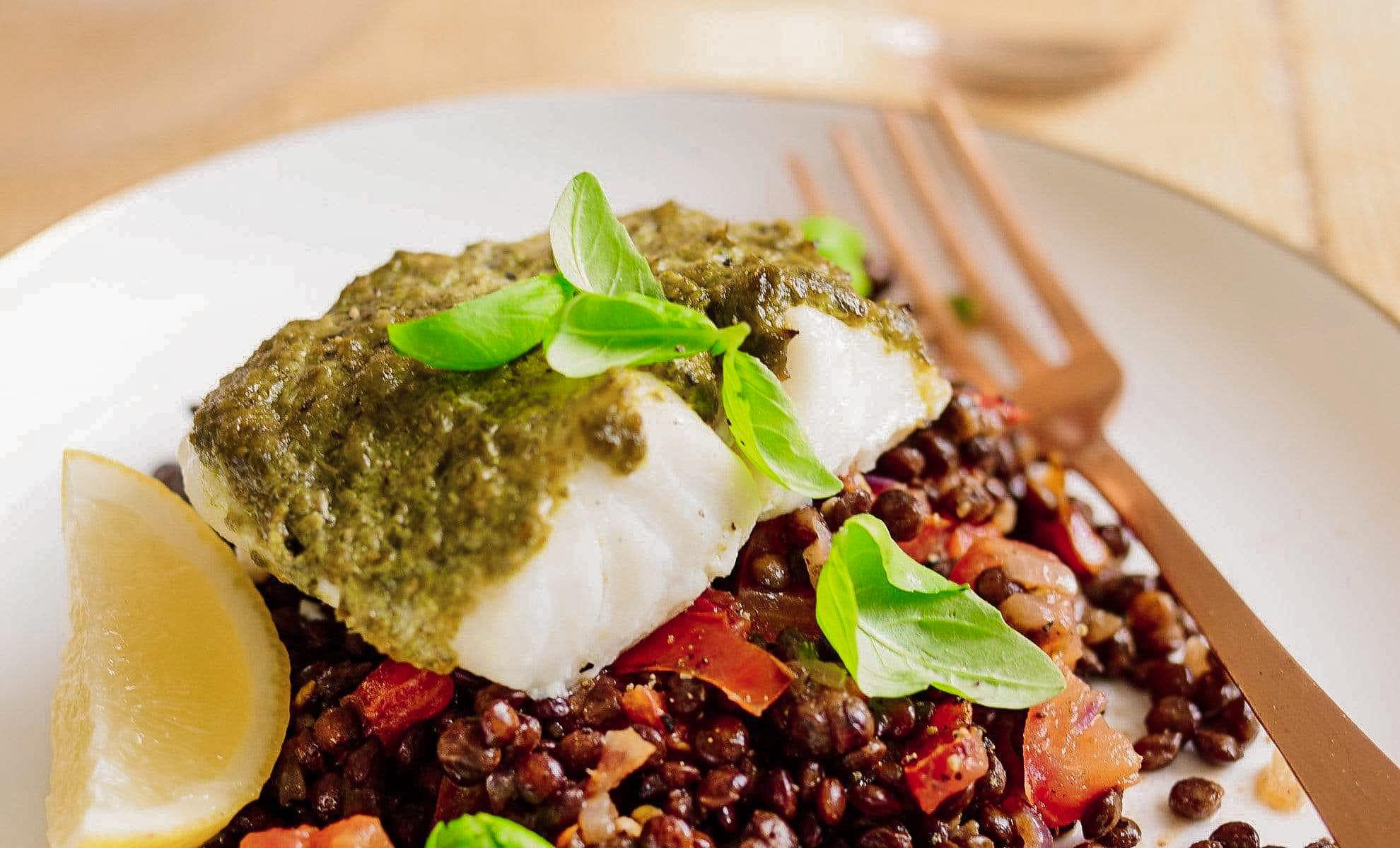 Le filet de cabillaud est recouvert de pesto vert et il est disposé sur un mélange de lentilles et poivrons.