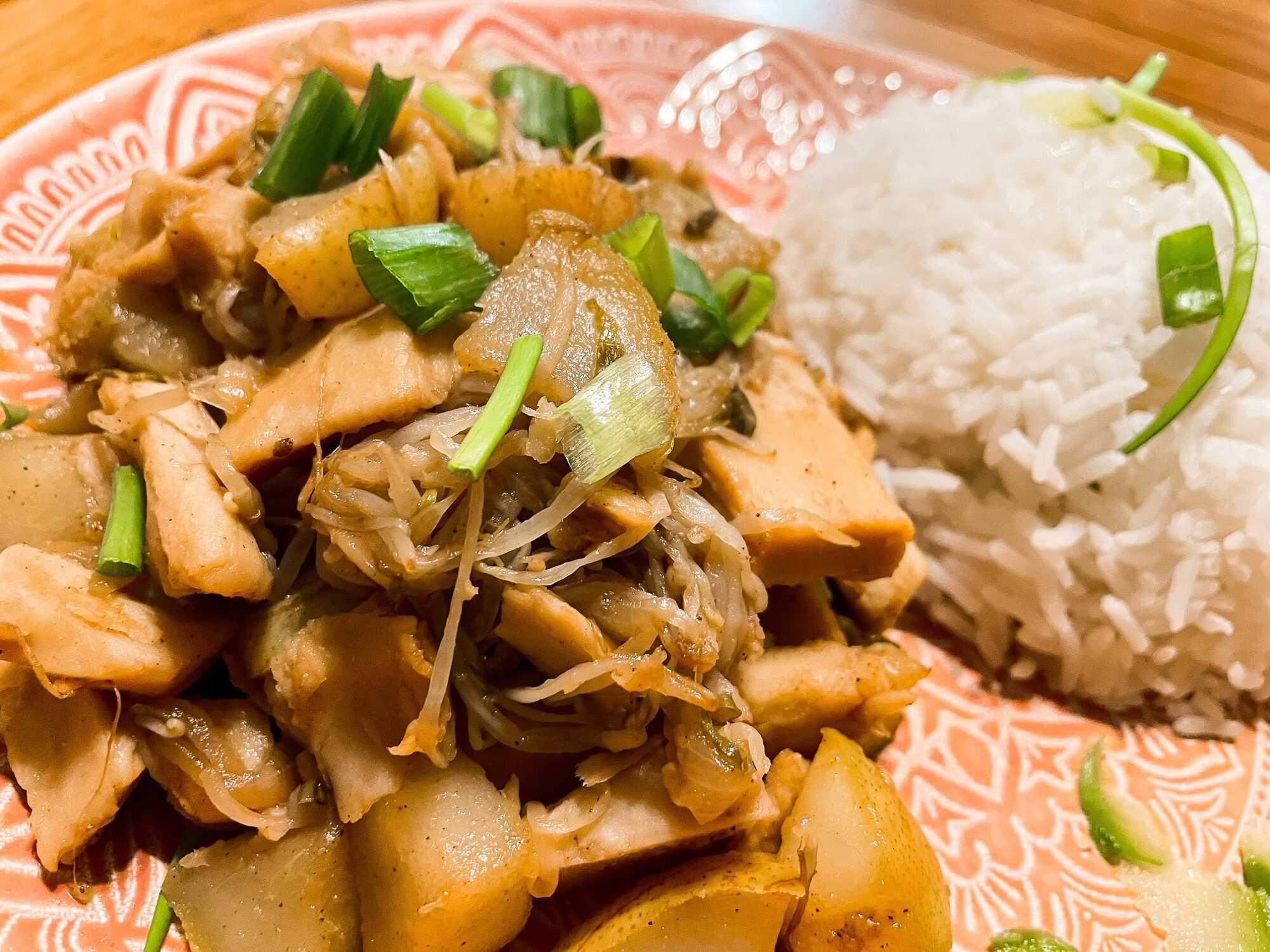 Les émincés de soja et poires caramélisées sont présentés dans une assiette rose et le plat est accompagné d'une boule de riz.