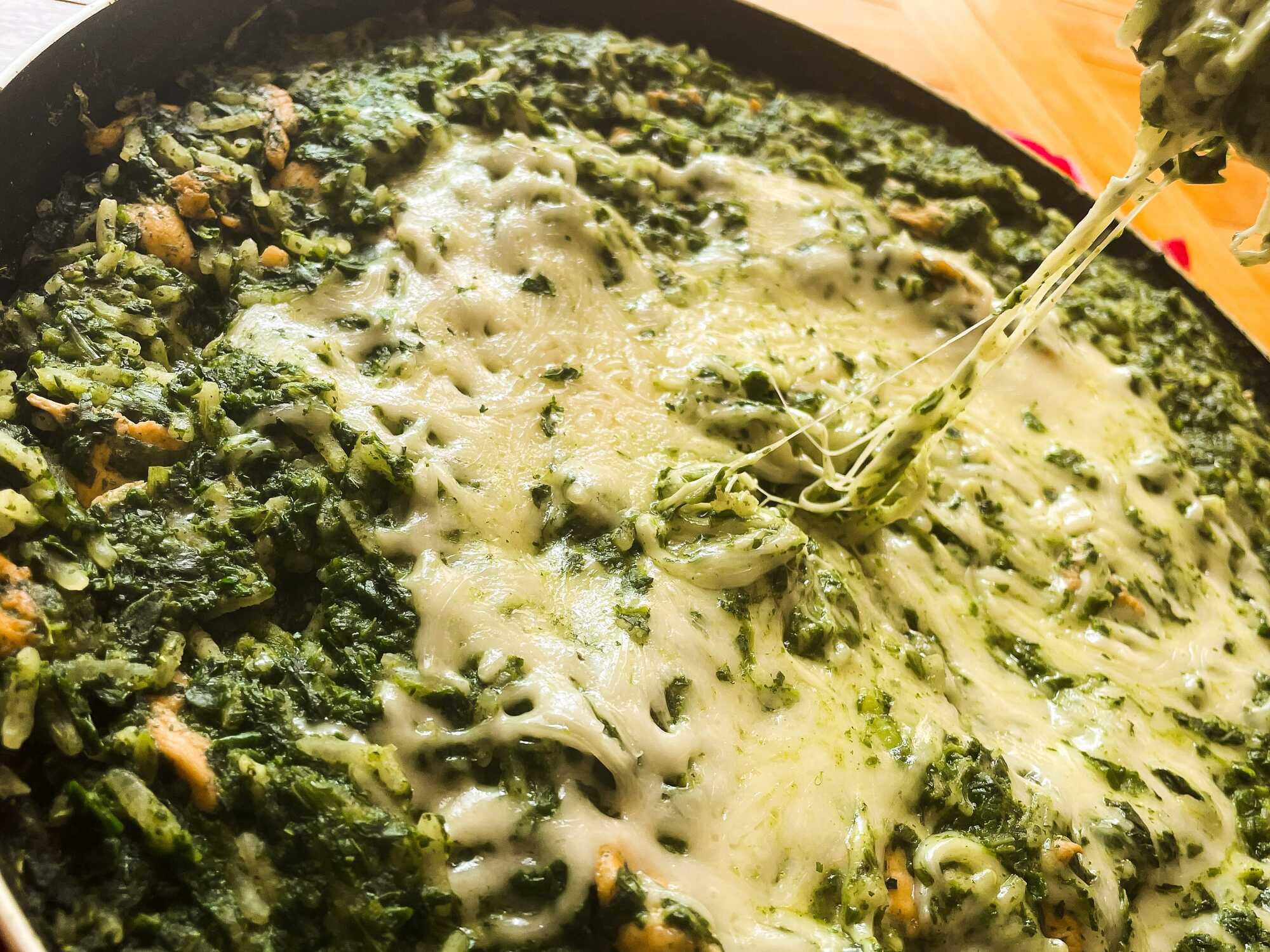 Le riz aux épinards est disposé dans une poêle avec un coeur de fromage fondant.