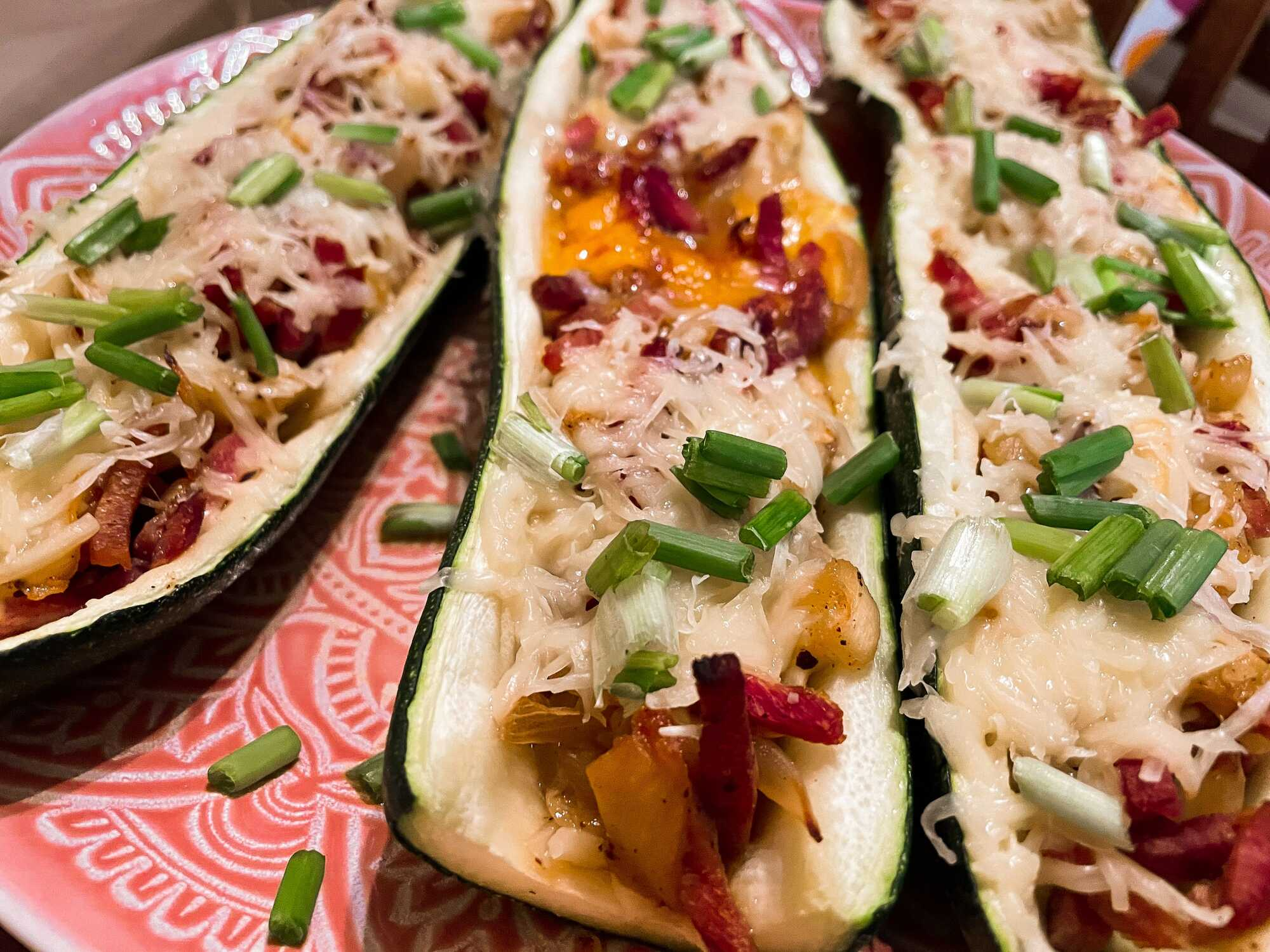 Les courgettes sont farcies de lardons, oeufs et fromage râpé et elles sont placées sur une assiette plate rose.