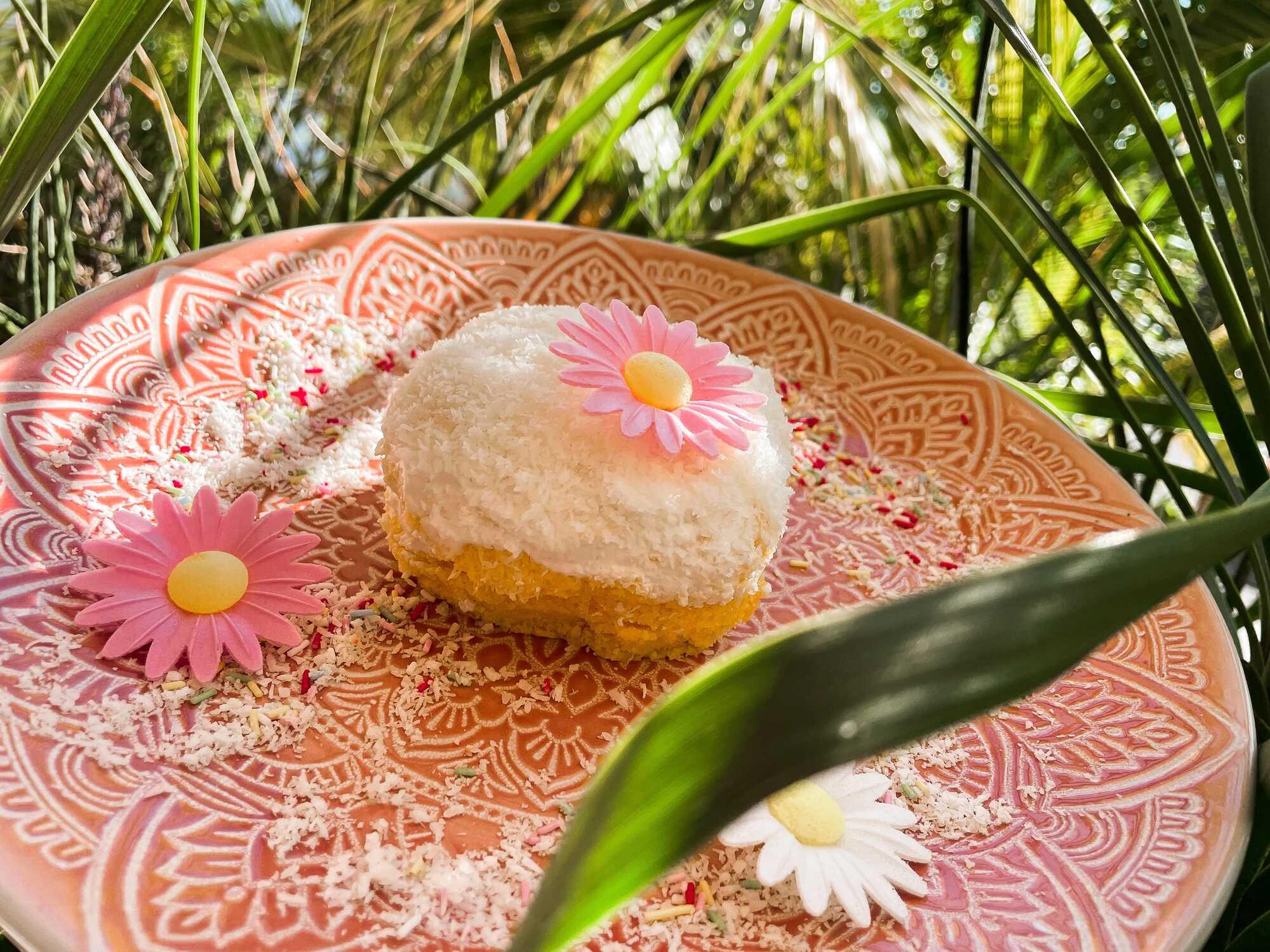 Le bowl cake est présenté dans une assiette rose, il est décoré d'un glaçage au chocolat blanc/noix de coco râpé avec des fleurs cosmetibles roses.
