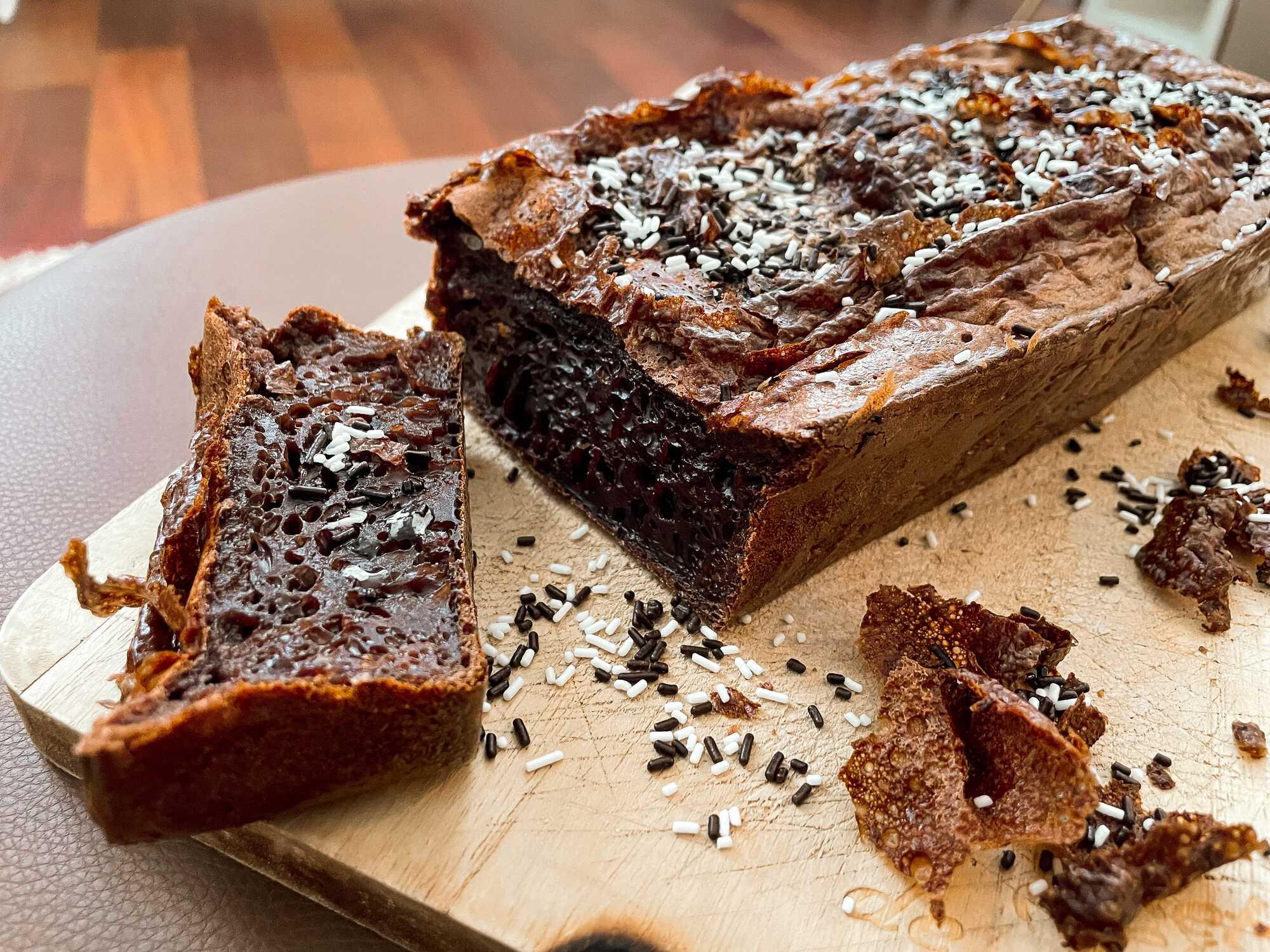 Le gâteau à la crème dessert chocolat est décoré de vermicelles au chocolat et il est posé sur une planche en bois.