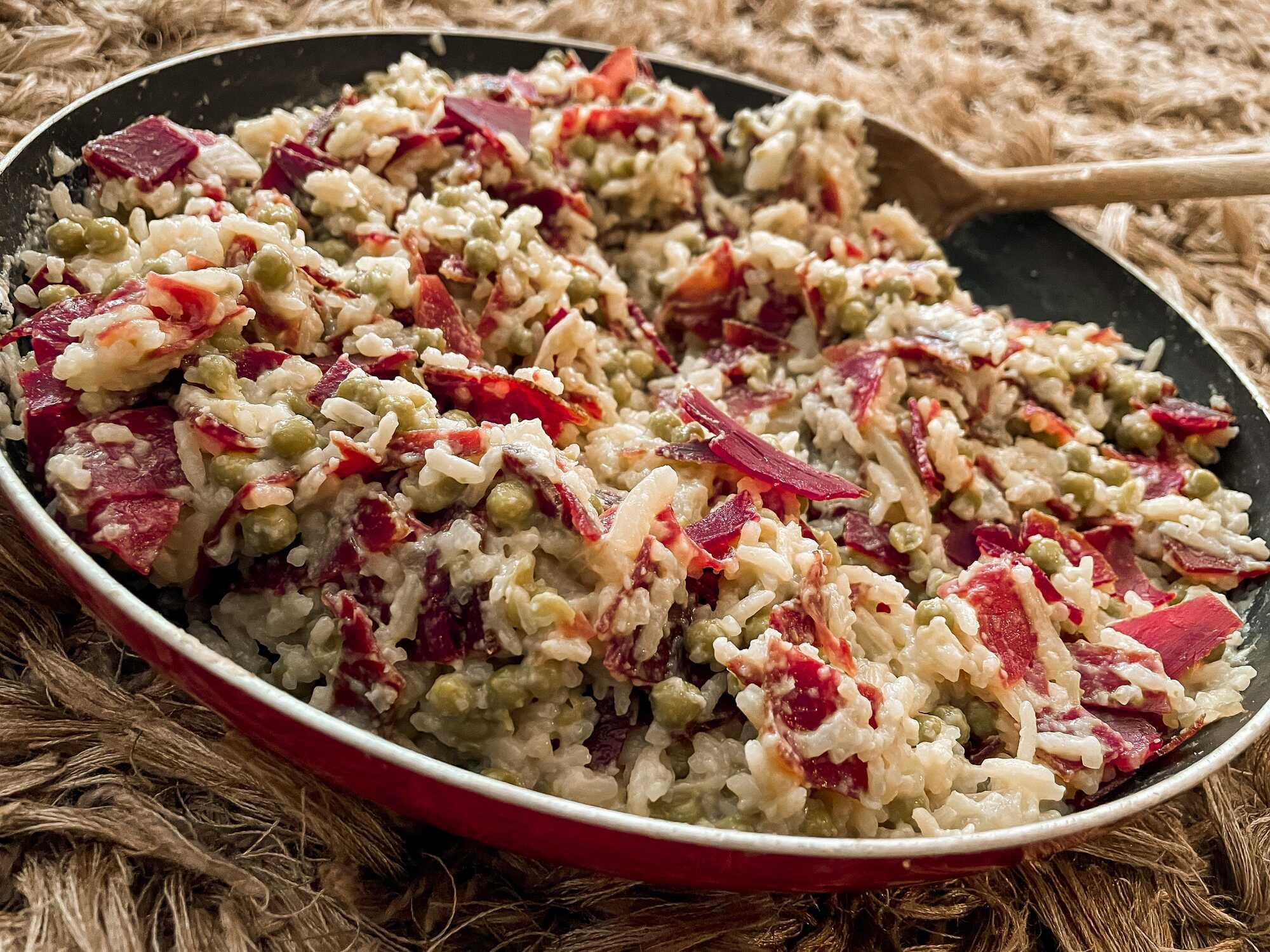 Le risotto de petits pois et viande des grisons est présenté dans une poêle, le plat est sur un fond marron.