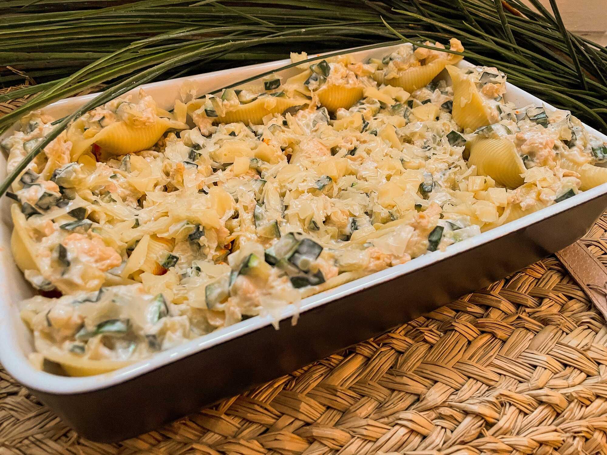 Les conchiglionis farcis aux courgettes, st-moret et poulet sont présentés dans un plat à gratin noir avec en arrière plan une plante.