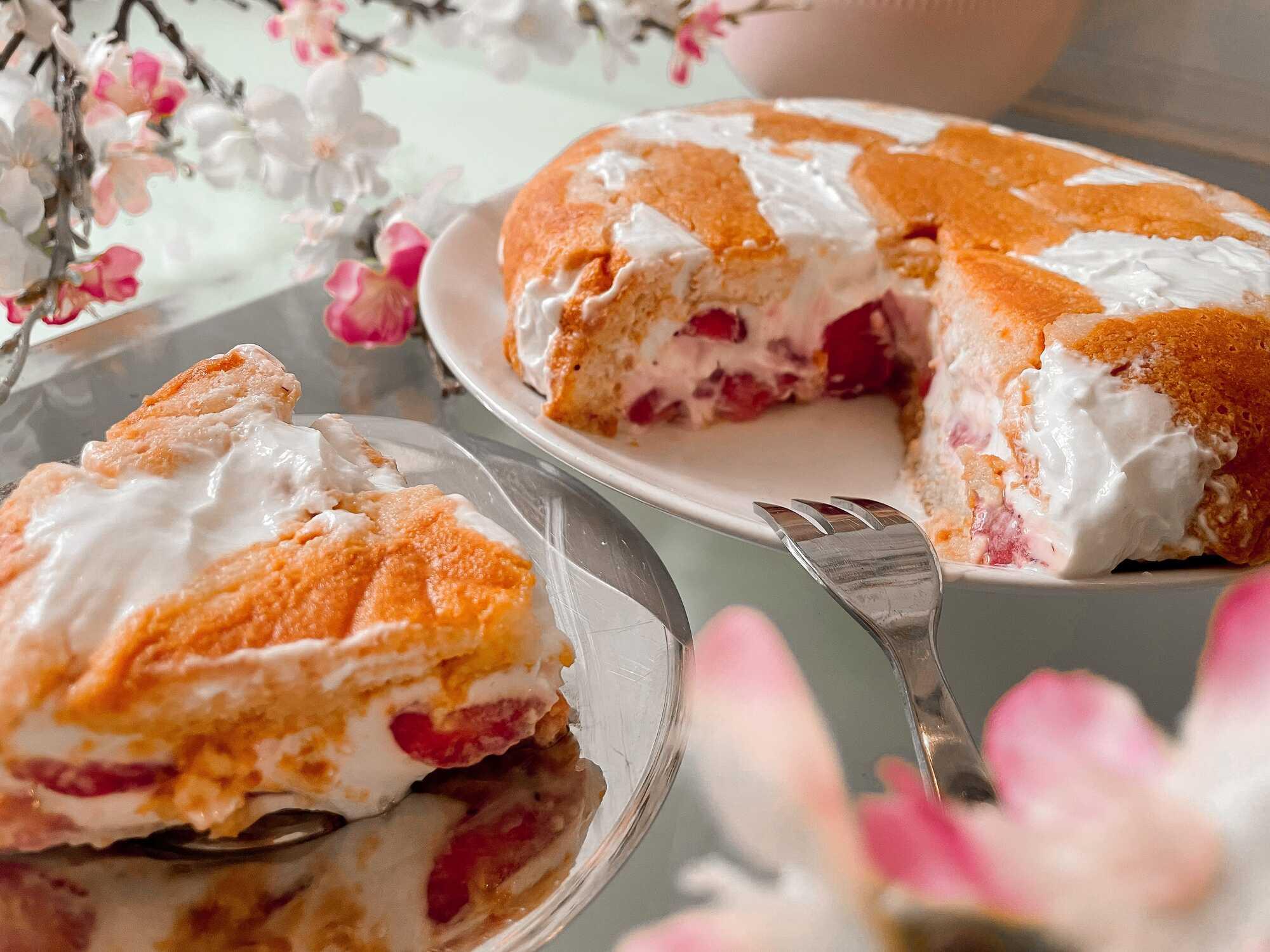 La charlotte aux fraises est présentée sur une assiette blanche en arrière plan et au premier plan il y a une part découpée.