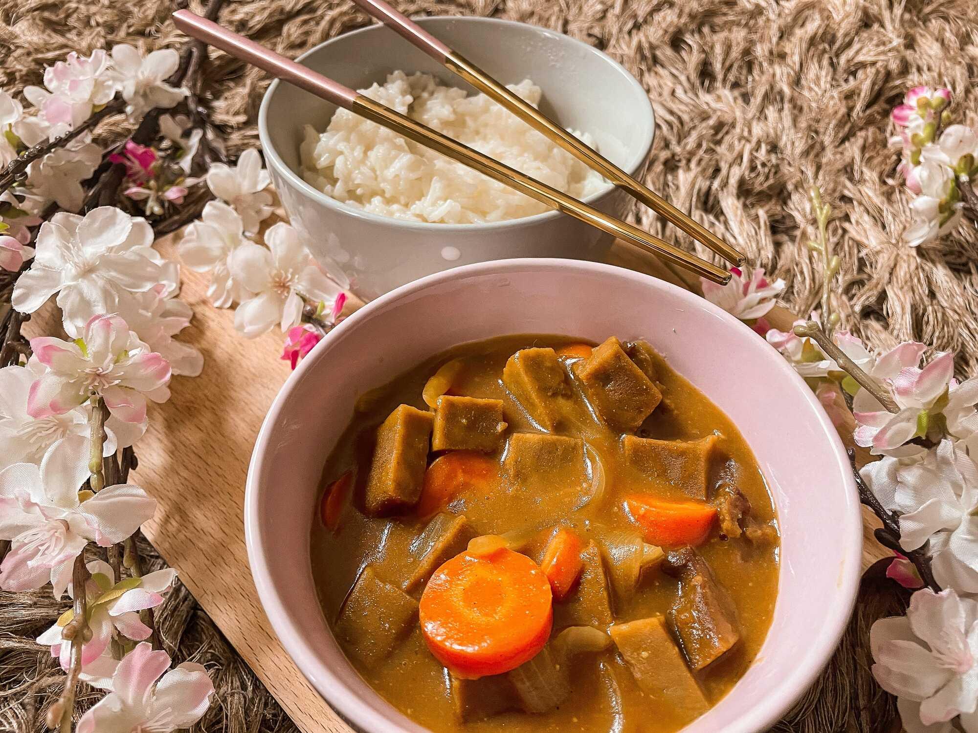 Le curry de seitan et carottes à la japonaise est accompagné d'un bol de riz à l'arrière plan, tout autour du curry il y a des fleurs de cerisier.