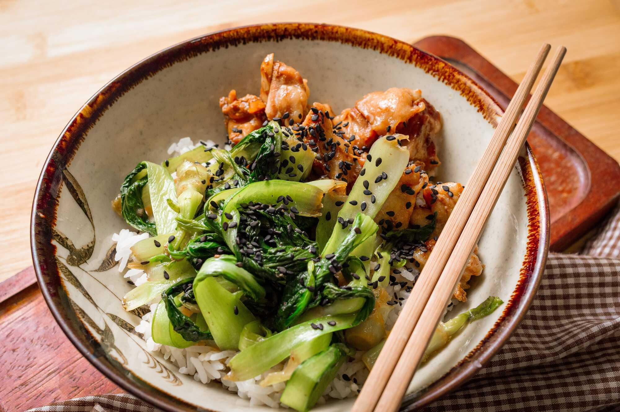Le poulet teriyaki et le pak choï sont au dessus d'une boule de riz, le tout présentés dans un bol à l'asiatique avec des baguettes.