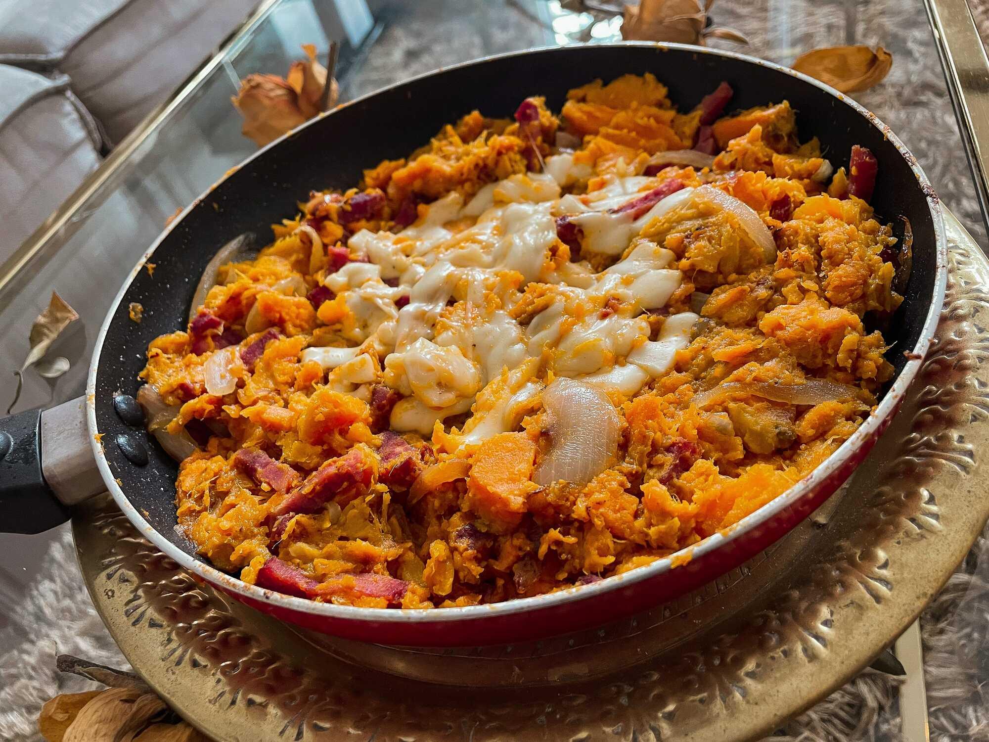 Les patates douces et lardons sont recouverts de fromage fondu et ils sont présentés dans une poêle rouge avec autour des feuilles séchées.