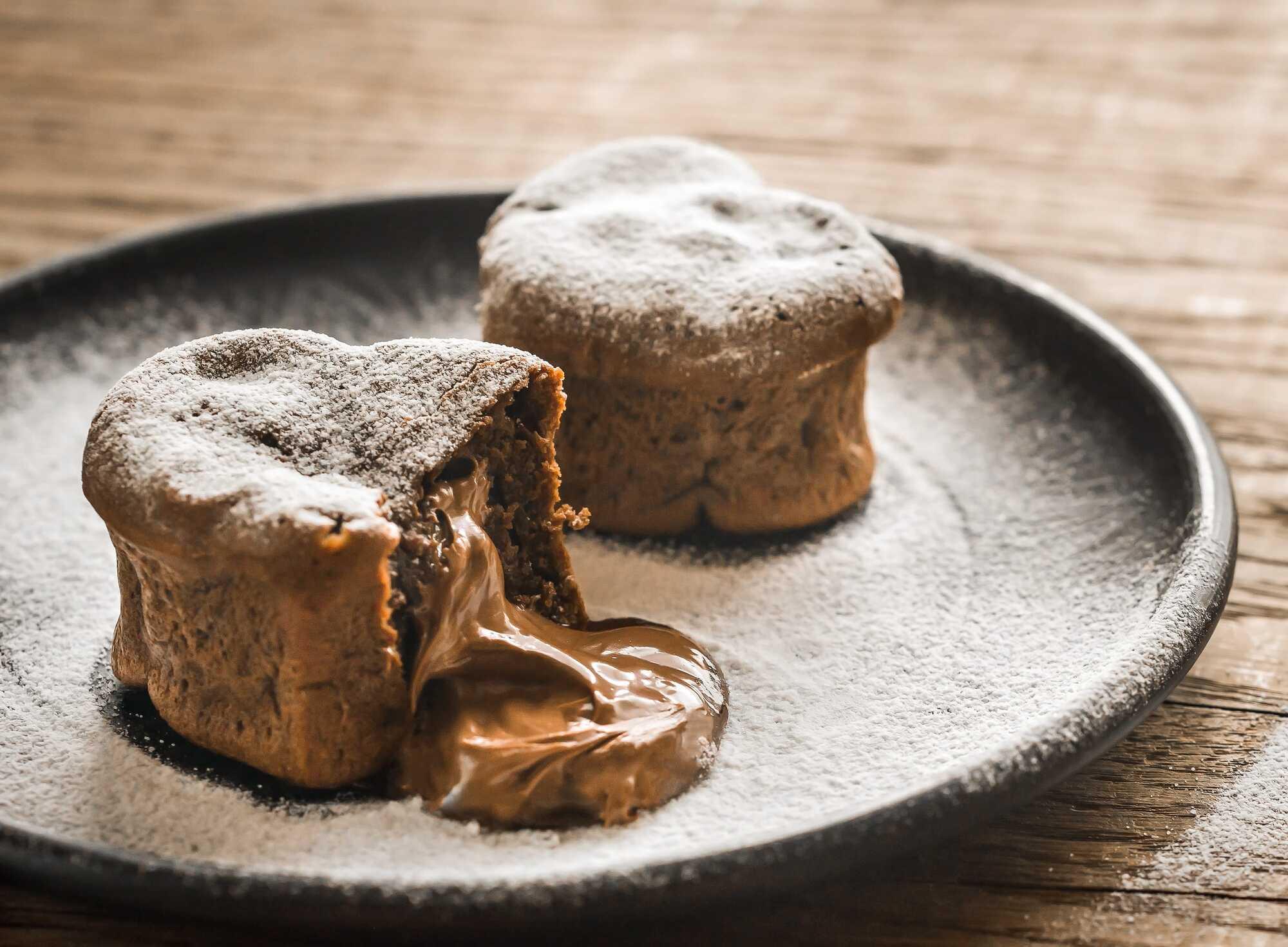 Dans un plat creux se trouve deux muffins dont l'un montre son coeur coulant, ils sont parsemés de sucre glace.