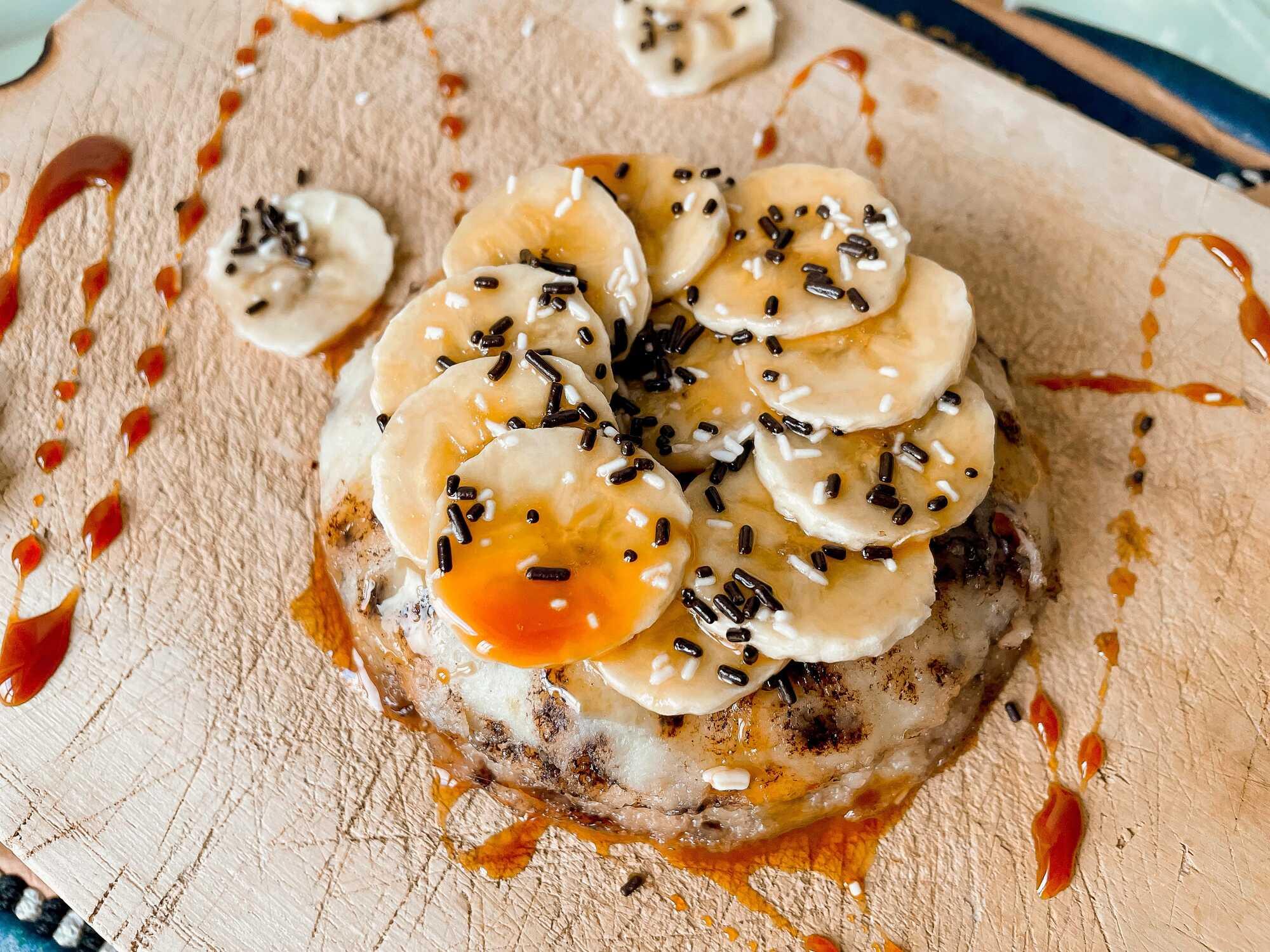 Le bowl cake protéiné est présenté sur une planche en bois et il est décoré de bananes et d'un nappage caramel sur le dessus.