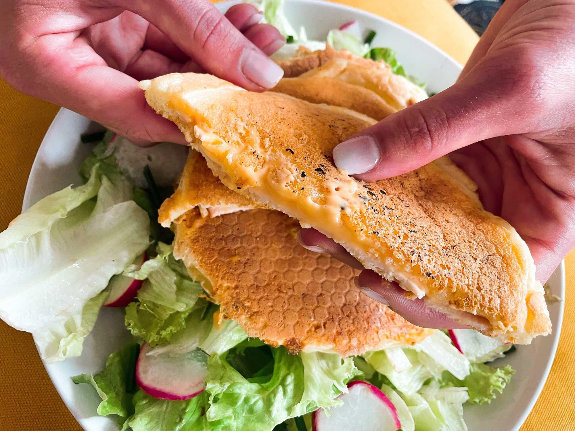 Les pancakes sont fourrés au cheddar et au blanc de poulet et ils sont accompagnés d'une salade verte.