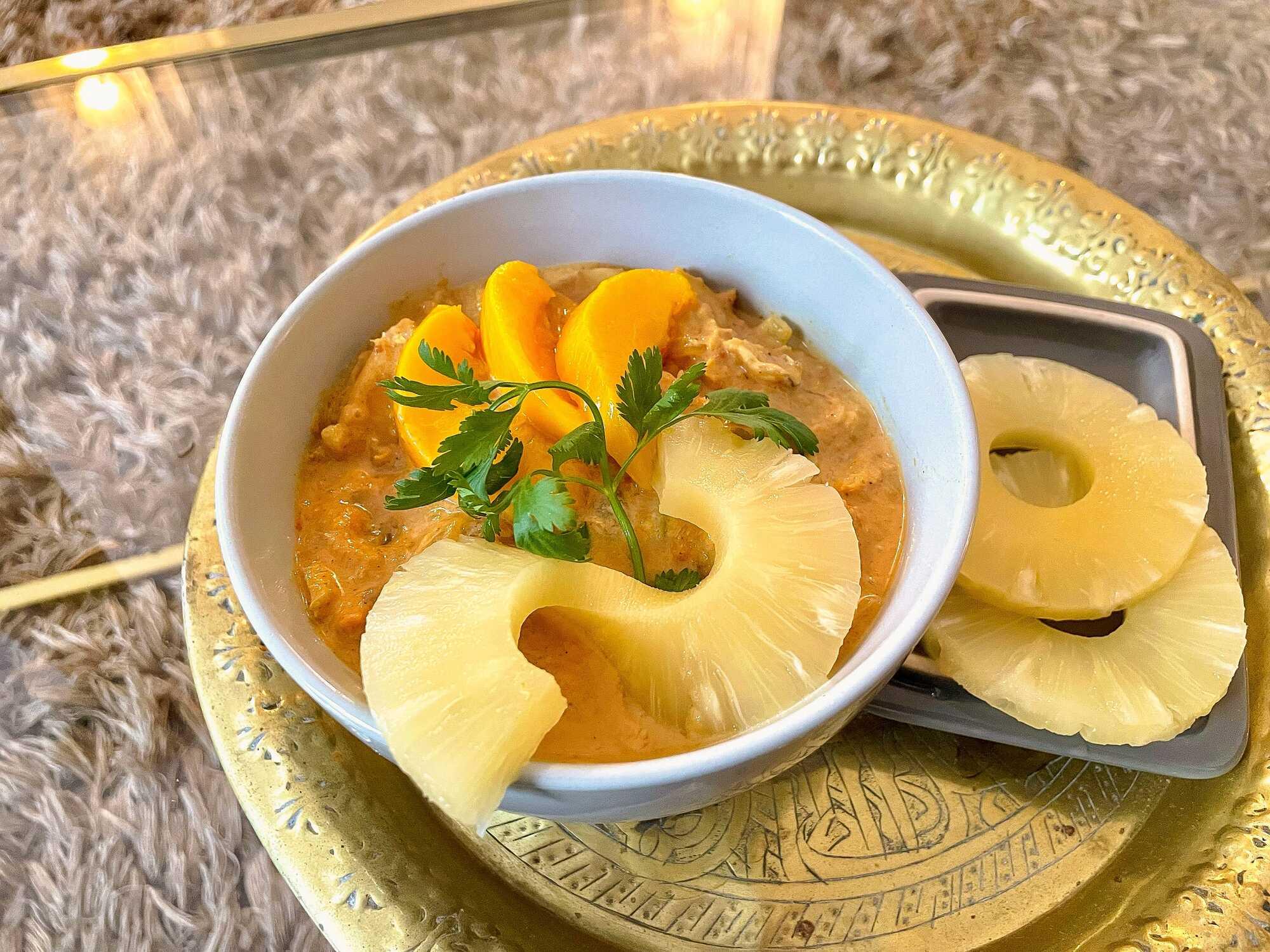 Le curry est présenté dans un bol avec des tranches d'ananas et de pêches sur le dessus, le tout posé sur un plateau doré.