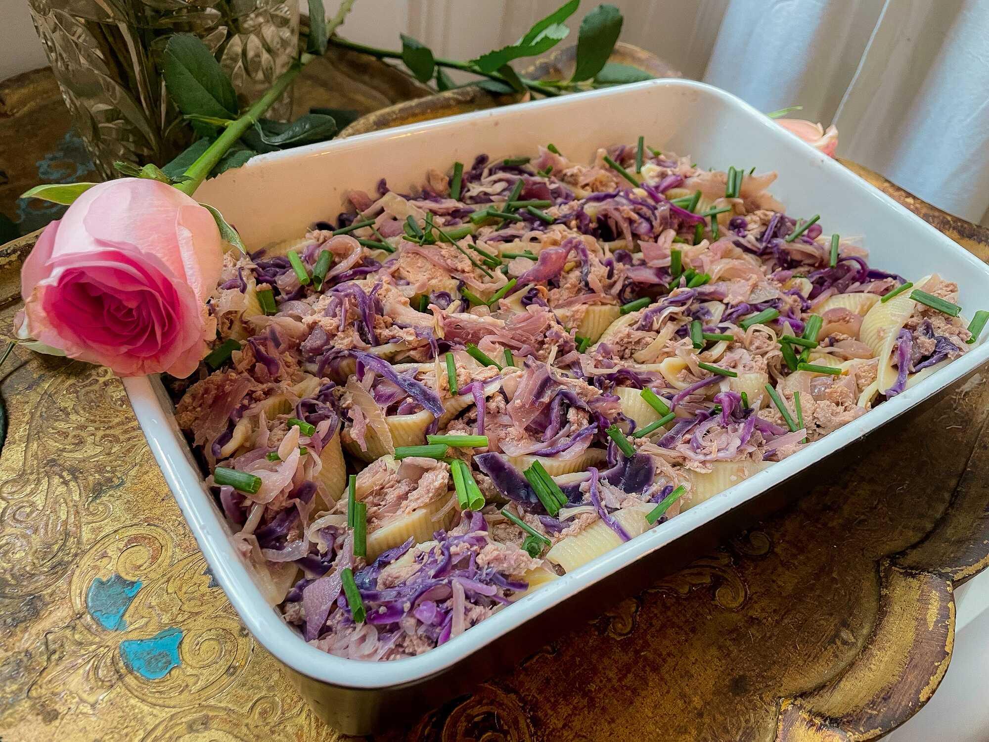Les conchiglionis sont fourrées avec du thon et du chou rouge dans un plat à gratin. Avec en décoration des roses.
