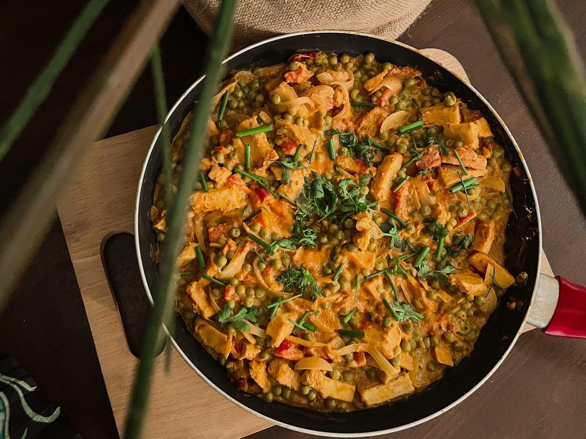 Le soja est cuisiné comme un curry avec des petites pois et de la tomate, le tout est présenté dans une poêle au milieu d'un feuillage.