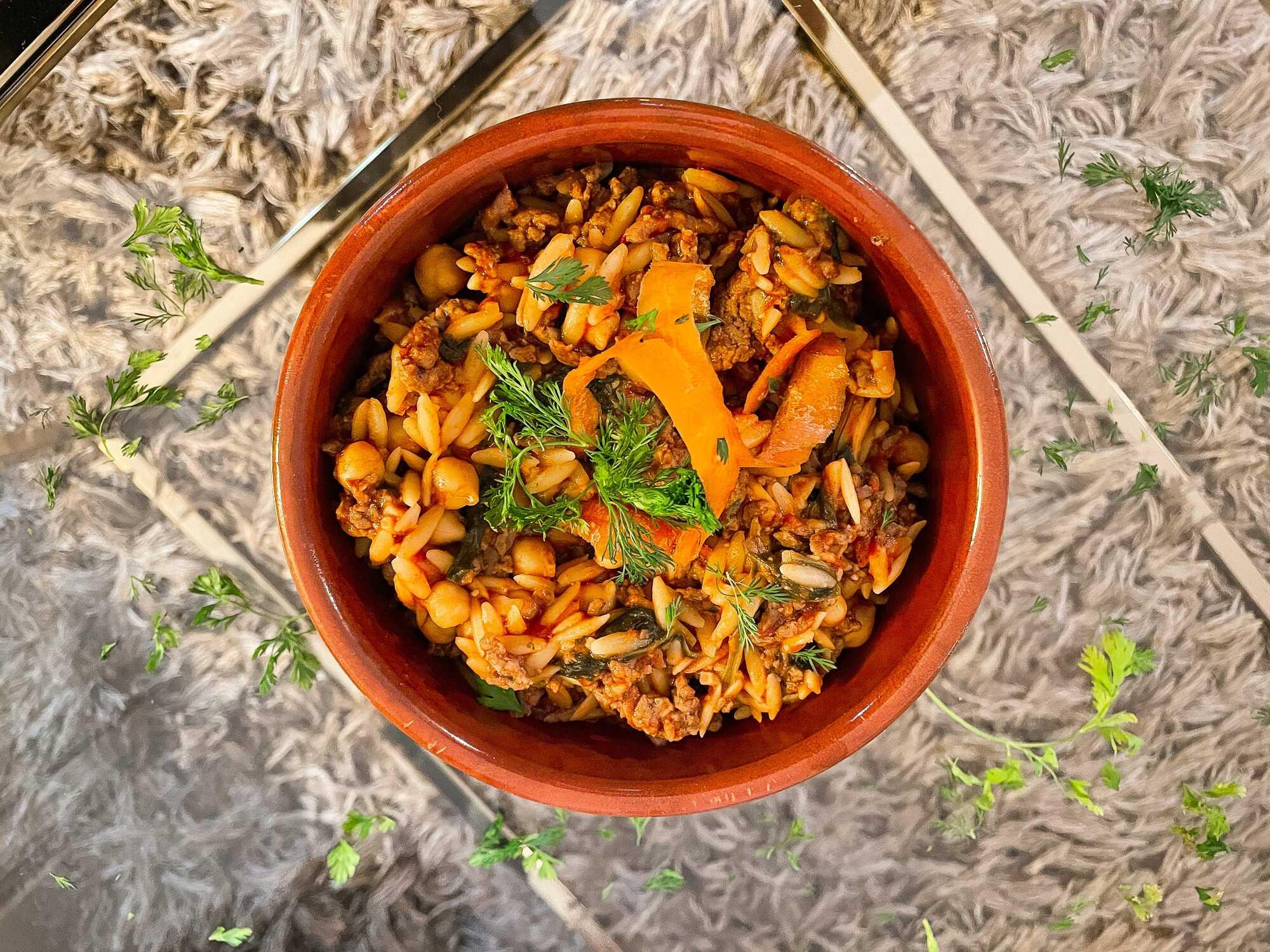 Le one pot orzo, épinards, boeuf et pois chiches est présenté dans un bol en céramique marron sur une table transparente.