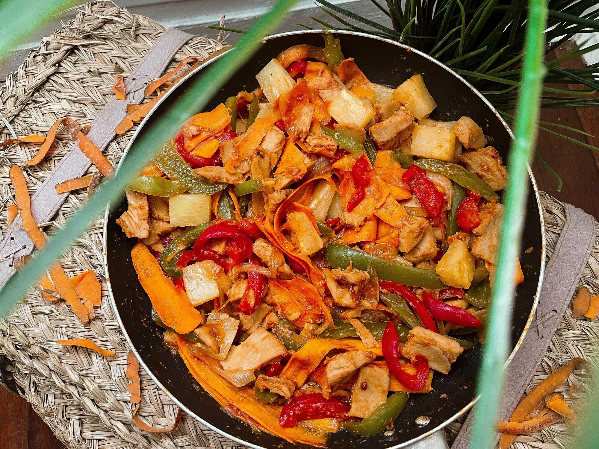 Le soja est cuisiné avec des poivrons, des carottes, de l'ananas et une sauce aigre-douce, le tout présenté dans une poêle au milieu de feuillage.