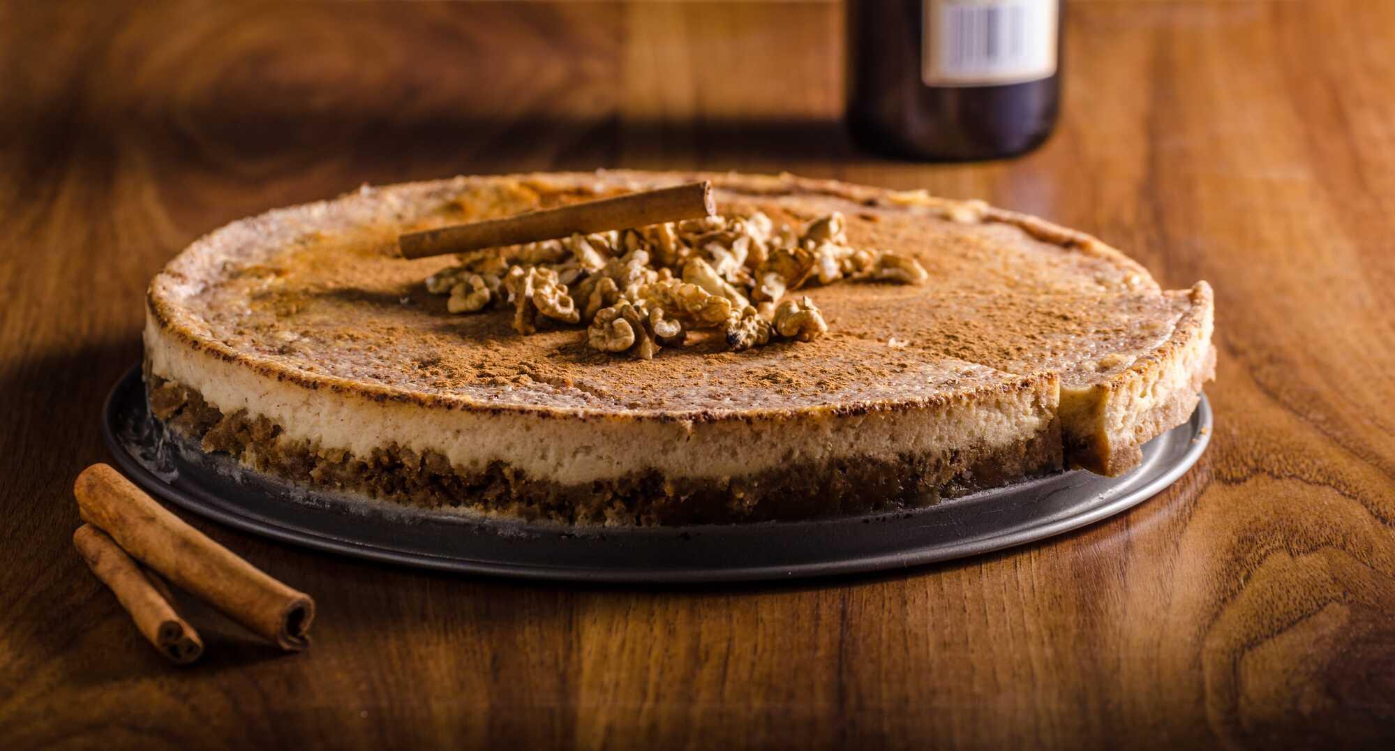 Présenté sur un plan de travail en bois foncé, le cheesecake est recouvert d'un topping au chocolat et de noix.