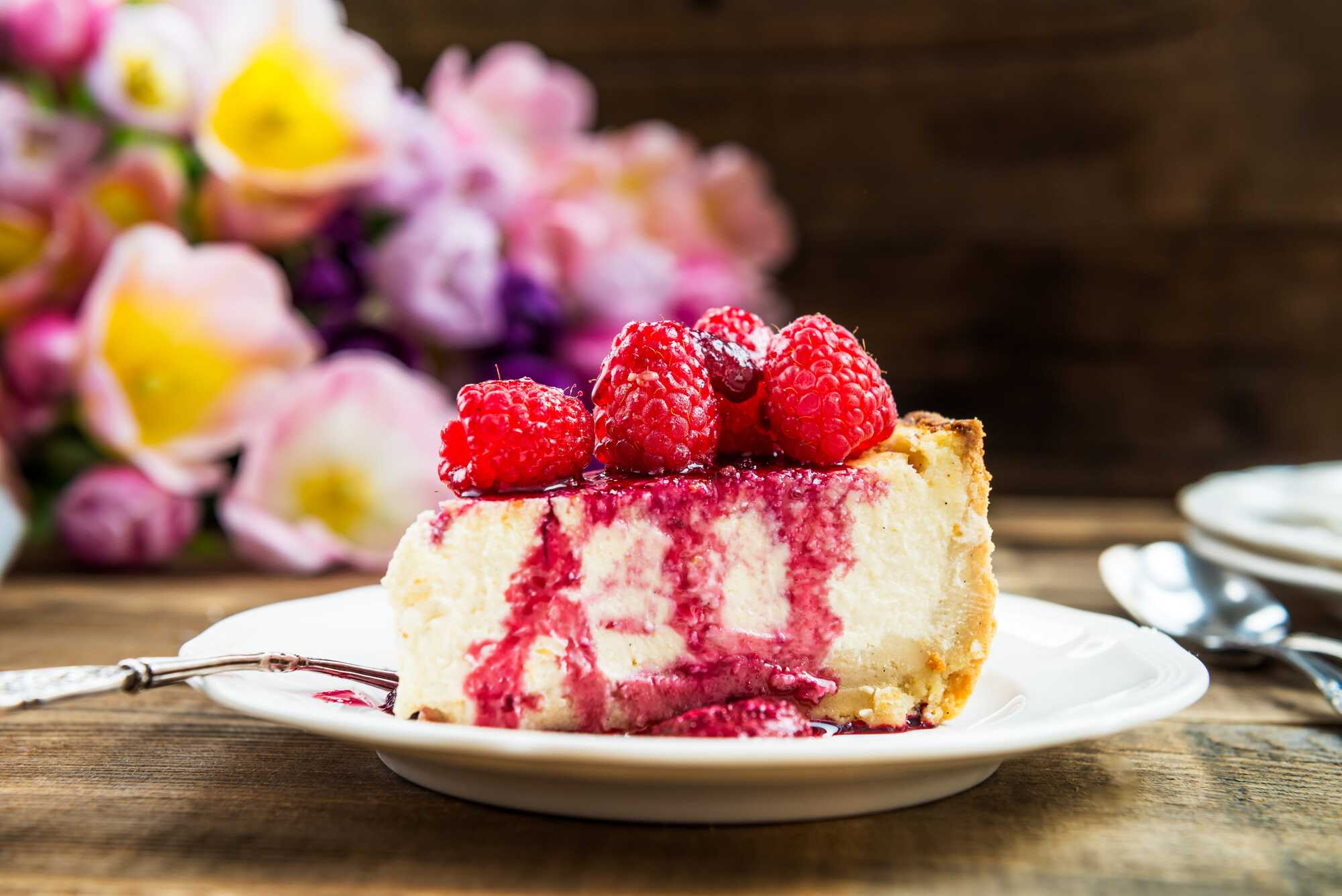 Posé sur une assiette de couleur blanche, un généreux morceau de cheesecake avec ses framboises.