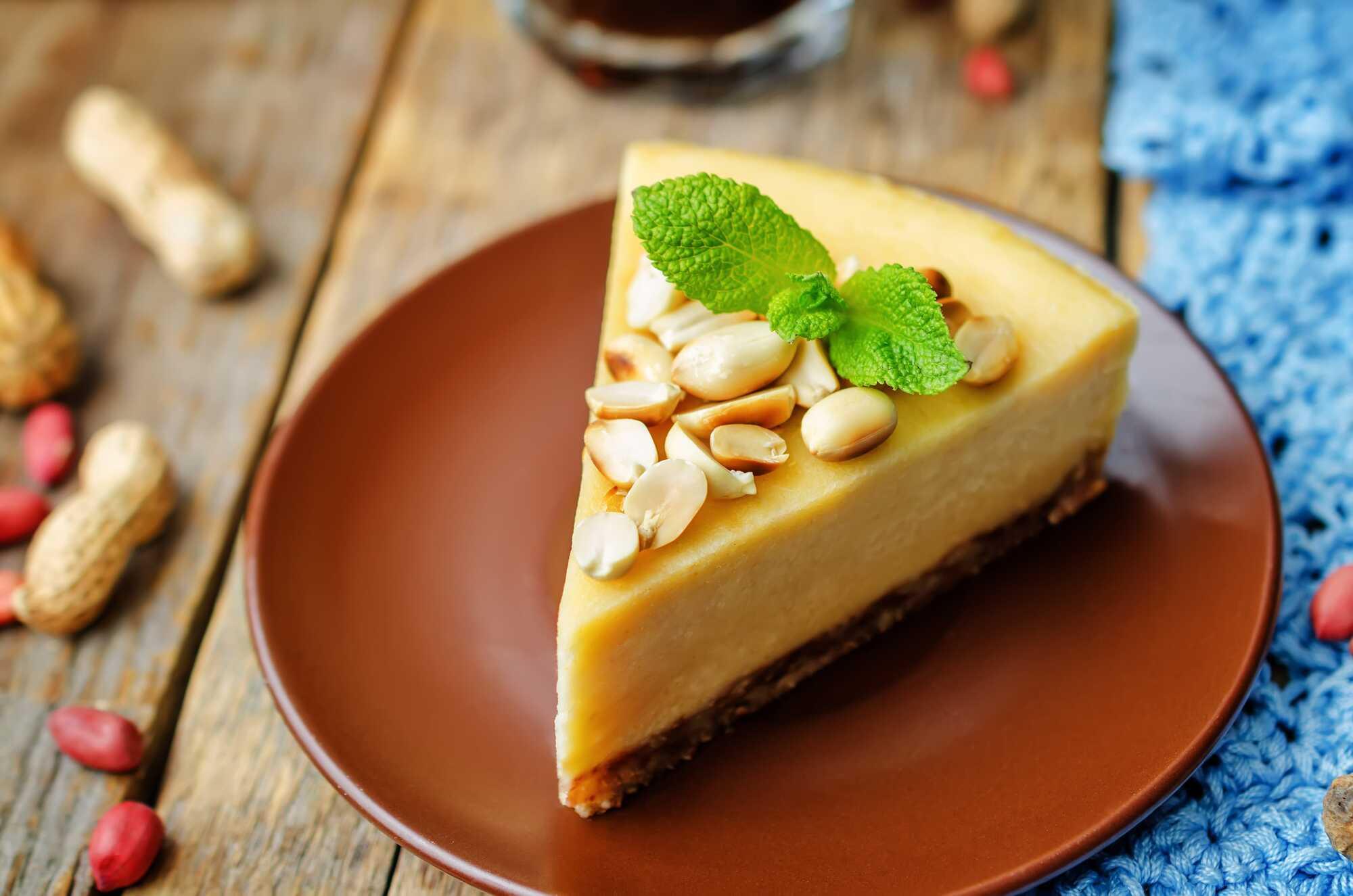 Une grosse et belle tranche de cheesecake montre tout son moelleux et les cacahuètes concassés sommairement sont disposés sur le dessus.
