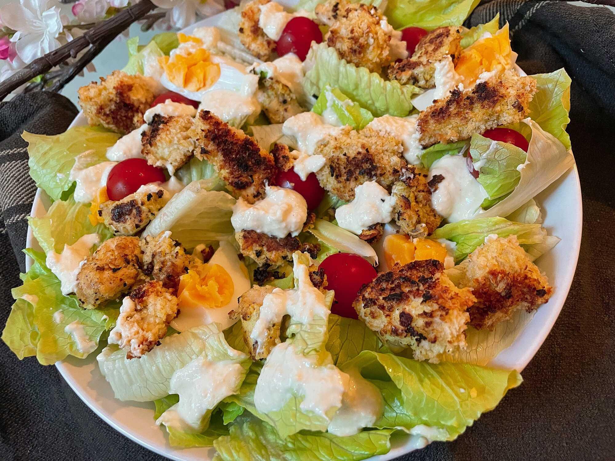 Cette salade est composée avec des tomates cerises, des oeufs, de la sauce blanche et des morceaux de poulet panés.