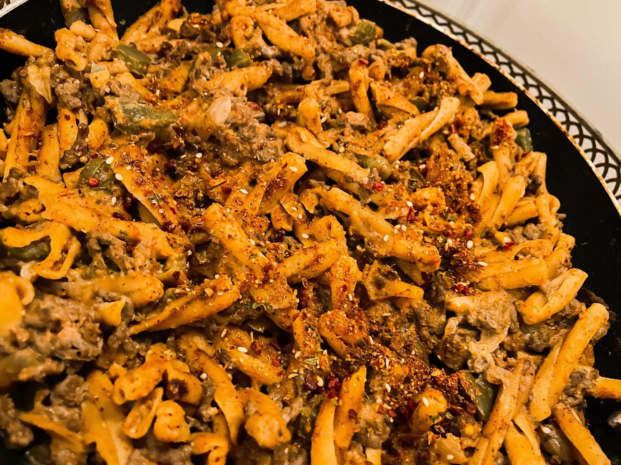Dans un plat à gratin, les différents ingrédients de la recette ont pris la couleur des tomates et des épices pour le plus bel effet.