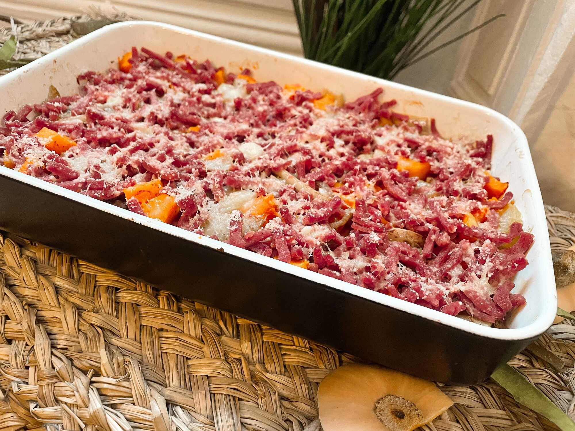 Sur un dessous de plat en raphia se trouve un plat à gratin contenant les allumettes de bacon, la courge butternut et le fromage gratiné.