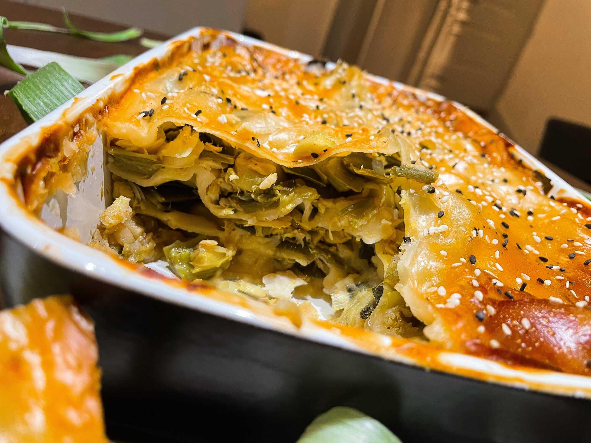 Dans un plat à gratin se trouve les lasagnes recouverts d'une couche de crème Béchamel. Une grosse partie a déjà été prélevée.