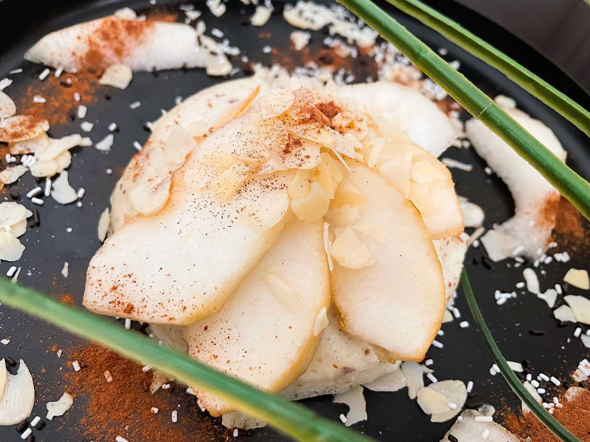 Déposées sur un plat de couleur noir, de grosses tranches de poire sont saupoudrées d'amandes effilées qui servent de topping.