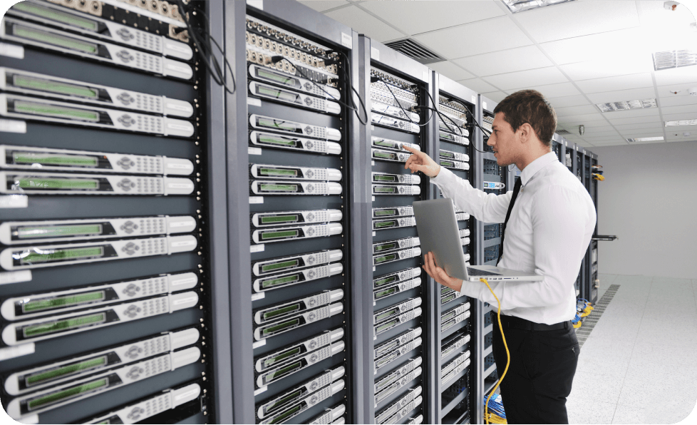 Man with laptop standing next to servers
