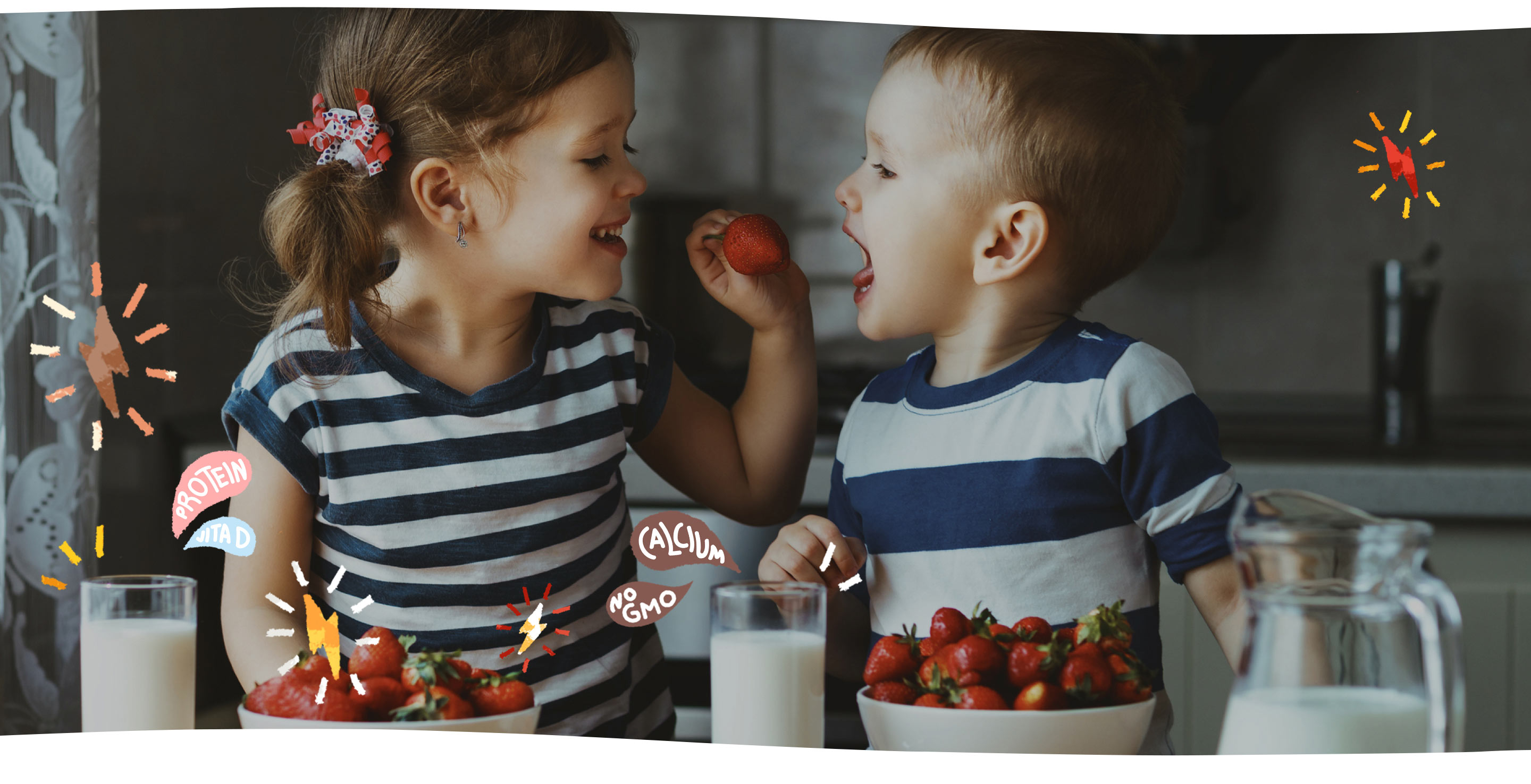 girl feeding strawberry to boy