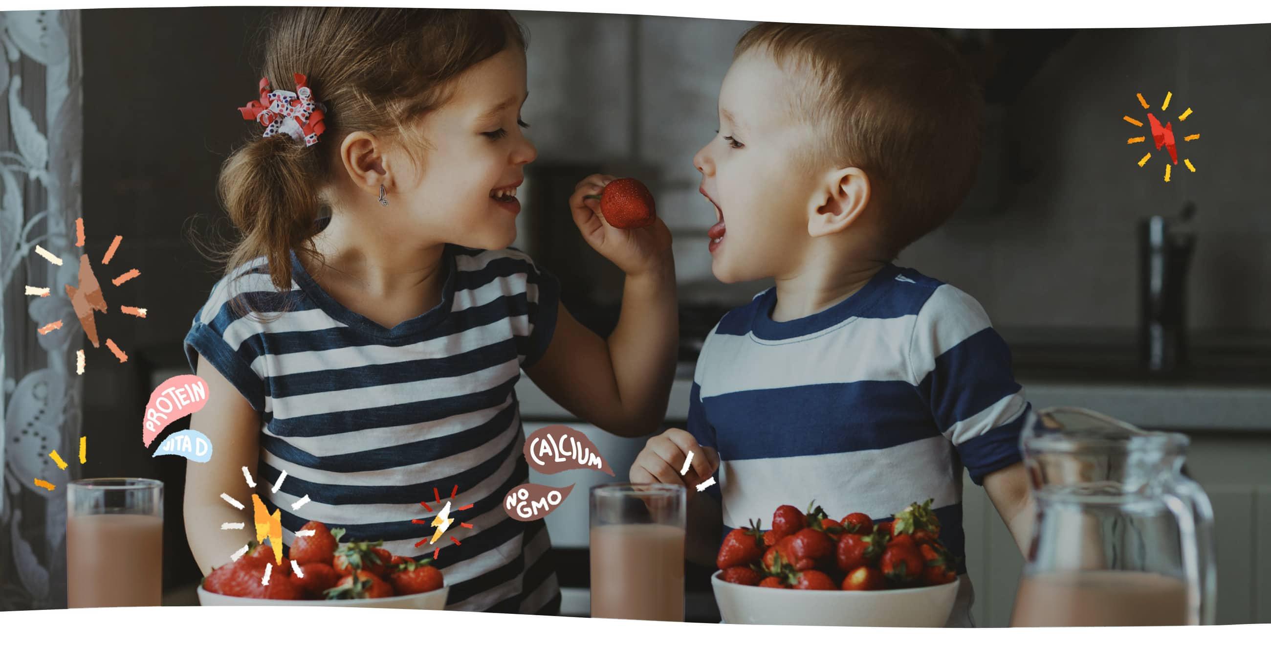 girl feeding strawberry to boy