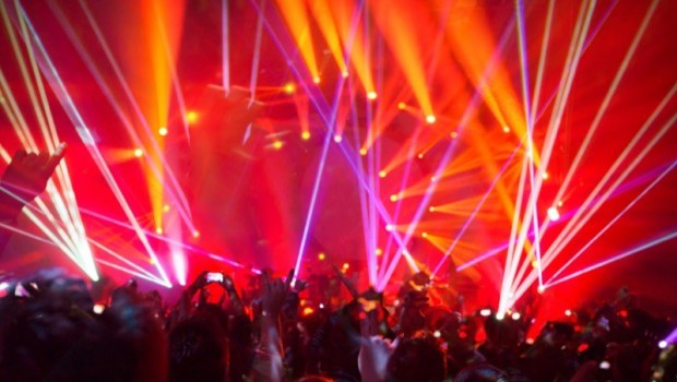 Image of colorful lights and attendees with cellphones at a concert