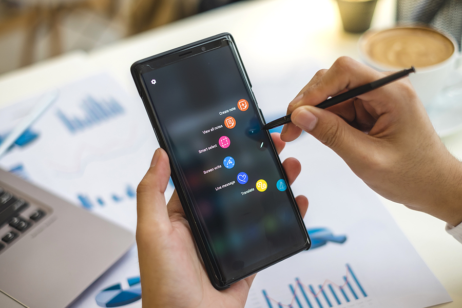 Close up hands of businessman holding pen of Samsung Galaxy Note9 and showing shortcut icons on the device screen while he working on the desk.