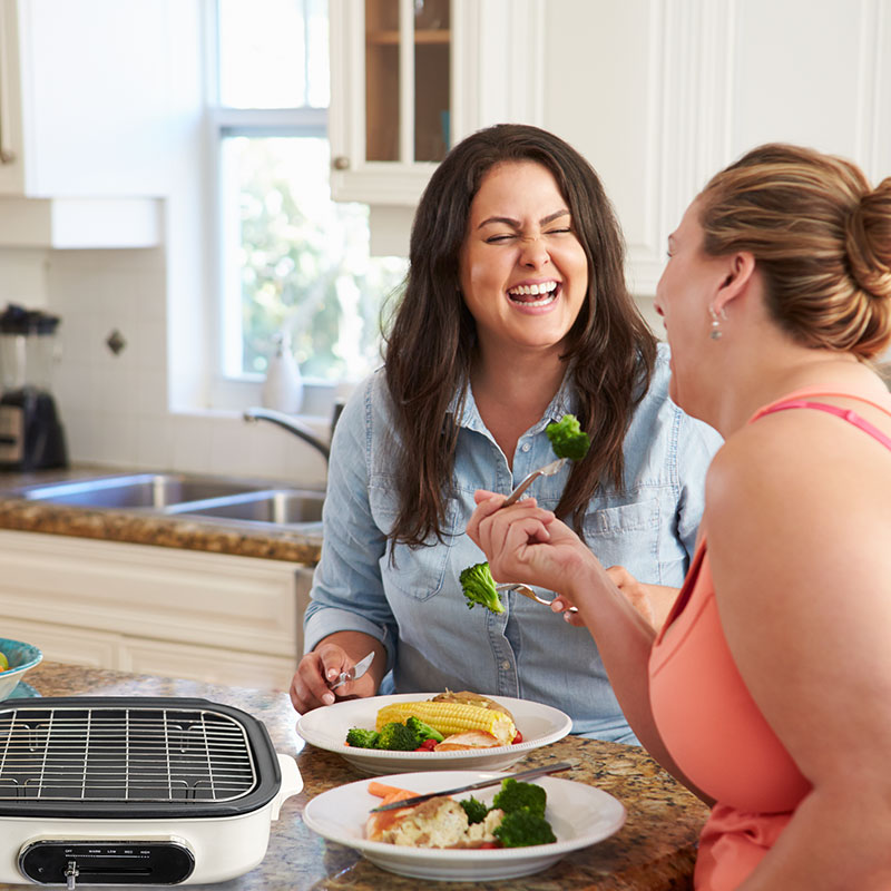 two women enjoying the meal they made on their electric skillet