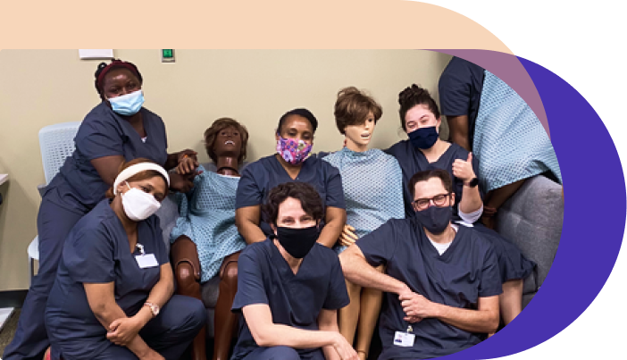 photo of nextstep learners in practice lab posing smiling for the camera with masks on, with them are our lab dummies Gerry and Grace