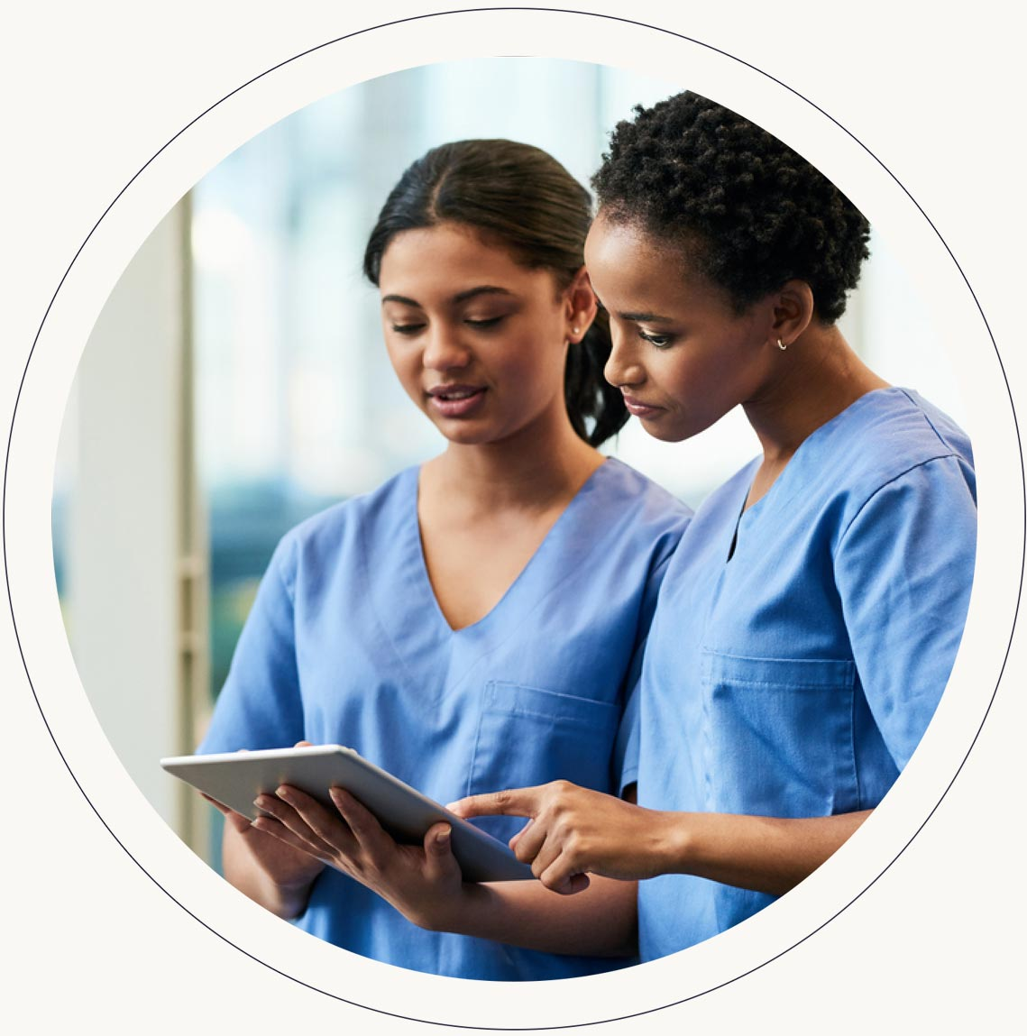 two nurses checking information on a tablet