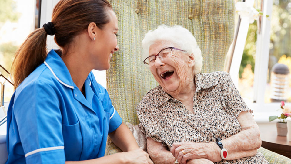 CNA laughing with an elderly woman