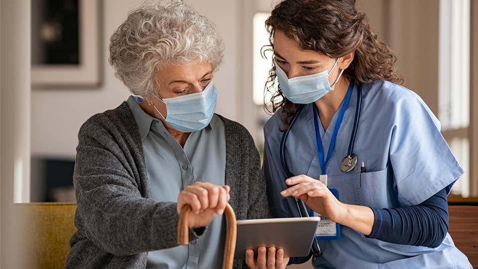 CNA working with older person on tablet