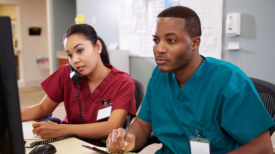 Two people choosing CNA programs online