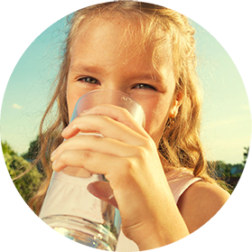 A young girl drinking a glass of clean drinking water